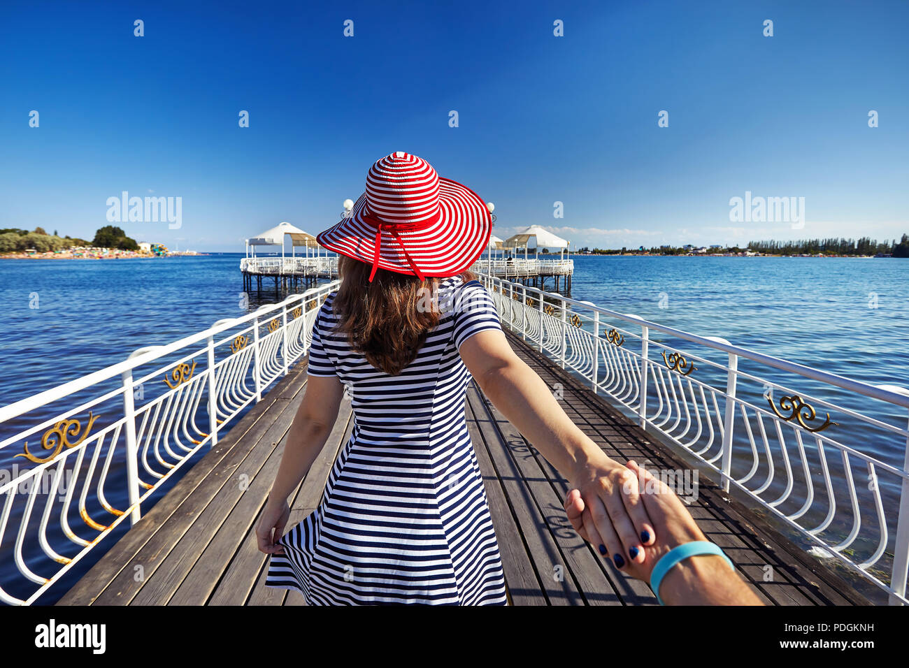 Woman in red Hat and striped dress holding his boyfriend by hand and walking to the pier in Ruh Ordo cultural complex at Issyk Kul lake with mountains - Stock Image