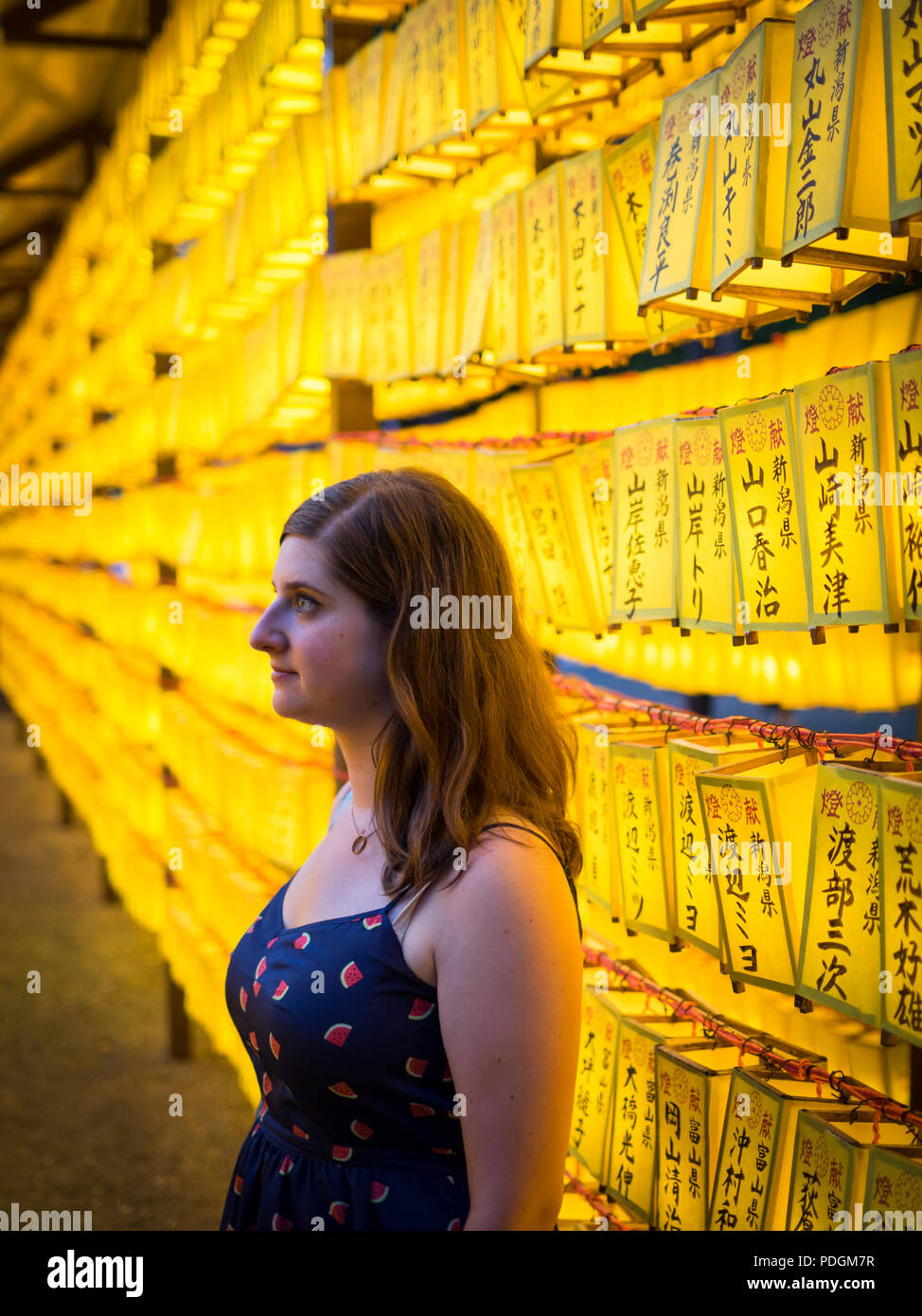 A tourist amongst lanterns of the 2018 Mitama Matsuri (Mitama Festival), a famous Japanese Obon (Bon) summer festival. Yasukuni Shrine, Tokyo, Japan. - Stock Image