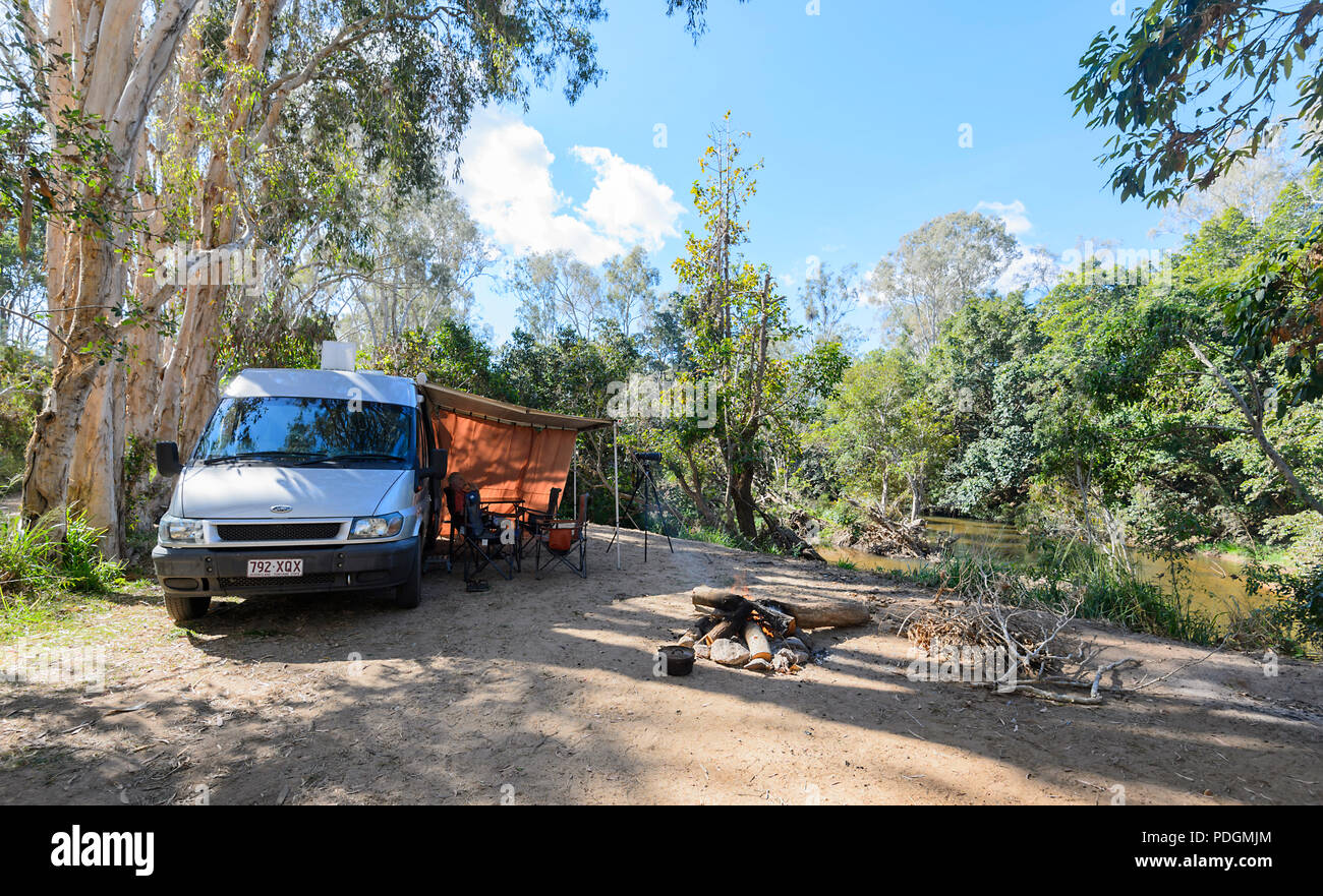 Ford Transit campervan in a shady campsite with a campfire by the Barron River, Biboohra, Far North Queensland, FNQ, QLD, Australia - Stock Image