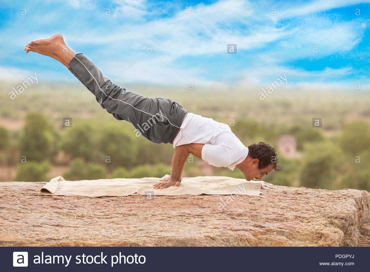 Young Indian man on top of mountain sitting in yoga pose. - Stock Image