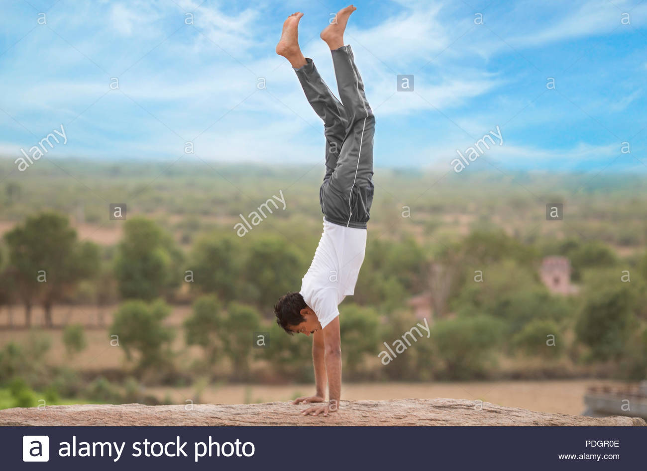 Young Indian man on top of mountain in adho mukha vrksasana  yoga pose. - Stock Image