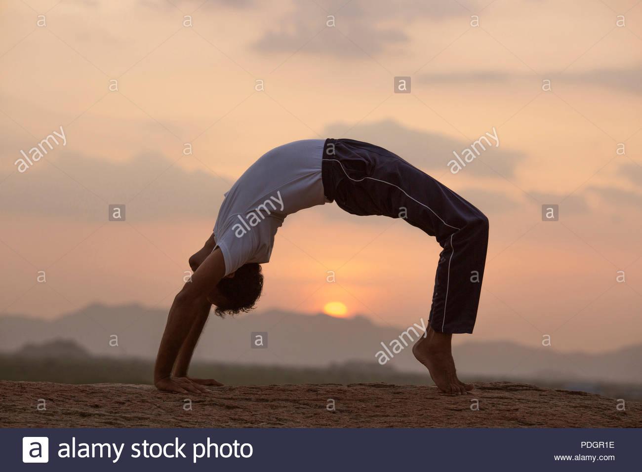 Young Indian man on top of mountain in Urdhva Dhanurasana yoga pose. - Stock Image