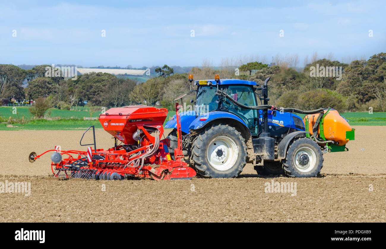 Planting seeds in a field with a New Holland tractor pulling a Kahn HR 3004 Trough and LC 302 Combiliner Venta seed drill in West Sussex, UK. - Stock Image