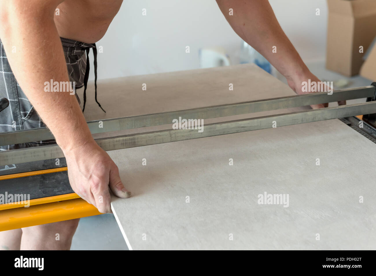 The Man Is Cutting The Floor Tiles Using A Tile Cutter Machine Stock