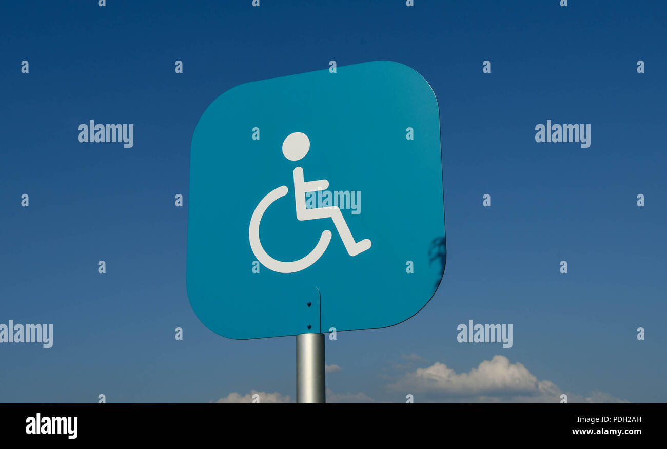 Blue metal sign with disability symbol above a parking bay in a supermarket car park reserved for disabled persons Stock Photo