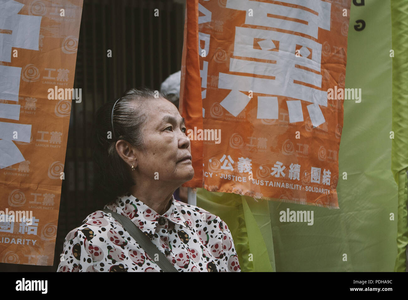 Hong Kong, Hong Kong, Hong Kong. 1st July, 2017. An elderly woman seen watching the crowd of demonstrators.Thousands came together and demonstrated to mark the 20th anniversary of the Handover from Britain to China, Hong Kong's return to China on July 1st 1997. The protestors marched through sun and rain from Victoria Park to Admiralty, taking a stand on a variety of human-rights-related causes. Credit: Viola Gaskell/SOPA Images/ZUMA Wire/Alamy Live News - Stock Image