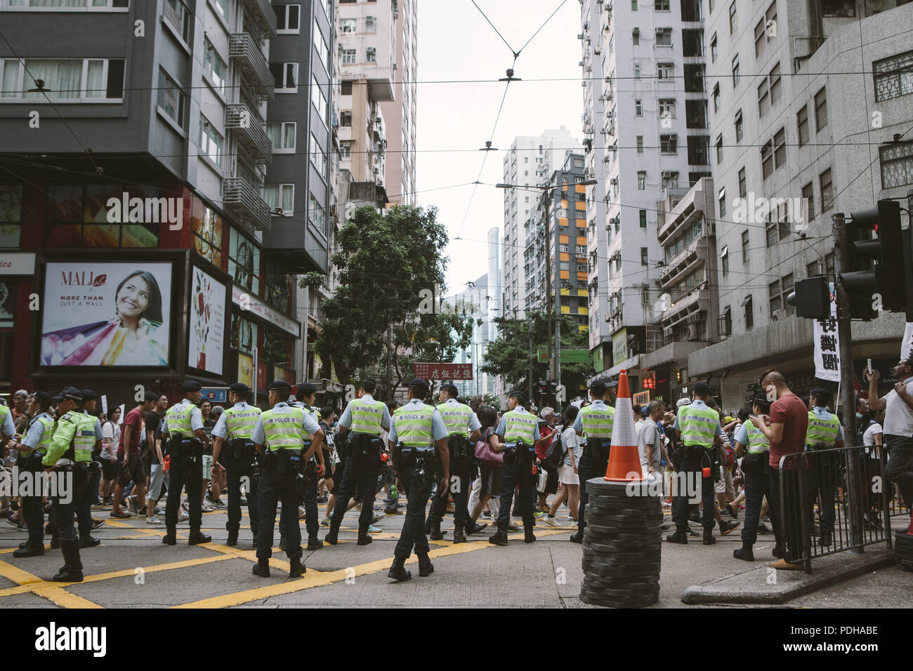 July 1, 2017 - Hong Kong, Hong Kong - Police seen monitoring the thousands of demonstrators marching..Thousands came together and demonstrated to mark the 20th anniversary of the Handover from Britain to China, Hong Kong's return to China on July 1st 1997. The protestors marched through sun and rain from Victoria Park to Admiralty, taking a stand on a variety of human-rights-related causes. (Credit Image: © Viola Gaskell/SOPA Images via ZUMA Wire) - Stock Image