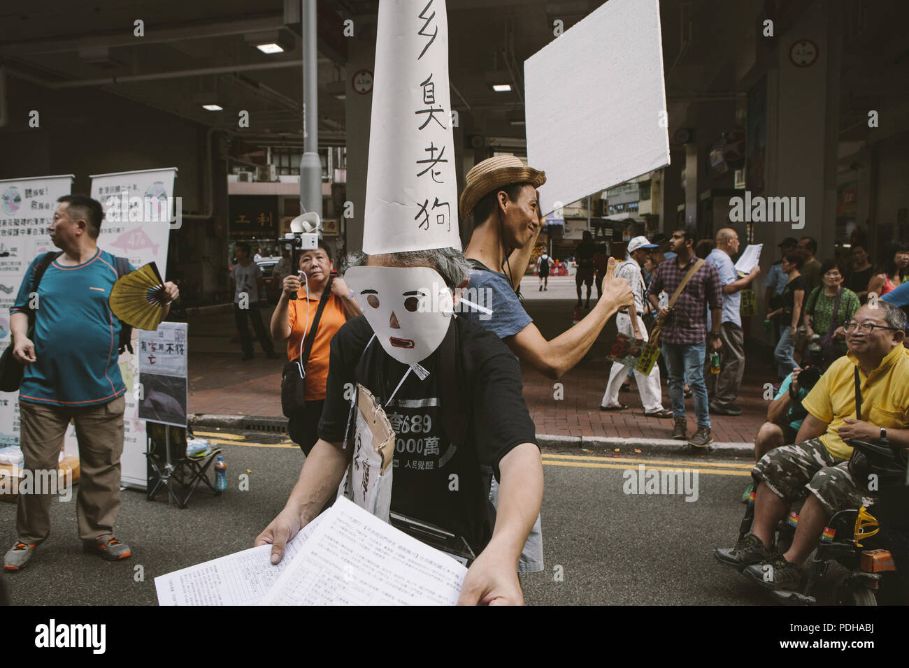 July 1, 2017 - Hong Kong, Hong Kong - A masked protester seen handing out fliers..Thousands came together and demonstrated to mark the 20th anniversary of the Handover from Britain to China, Hong Kong's return to China on July 1st 1997. The protestors marched through sun and rain from Victoria Park to Admiralty, taking a stand on a variety of human-rights-related causes. (Credit Image: © Viola Gaskell/SOPA Images via ZUMA Wire) - Stock Image