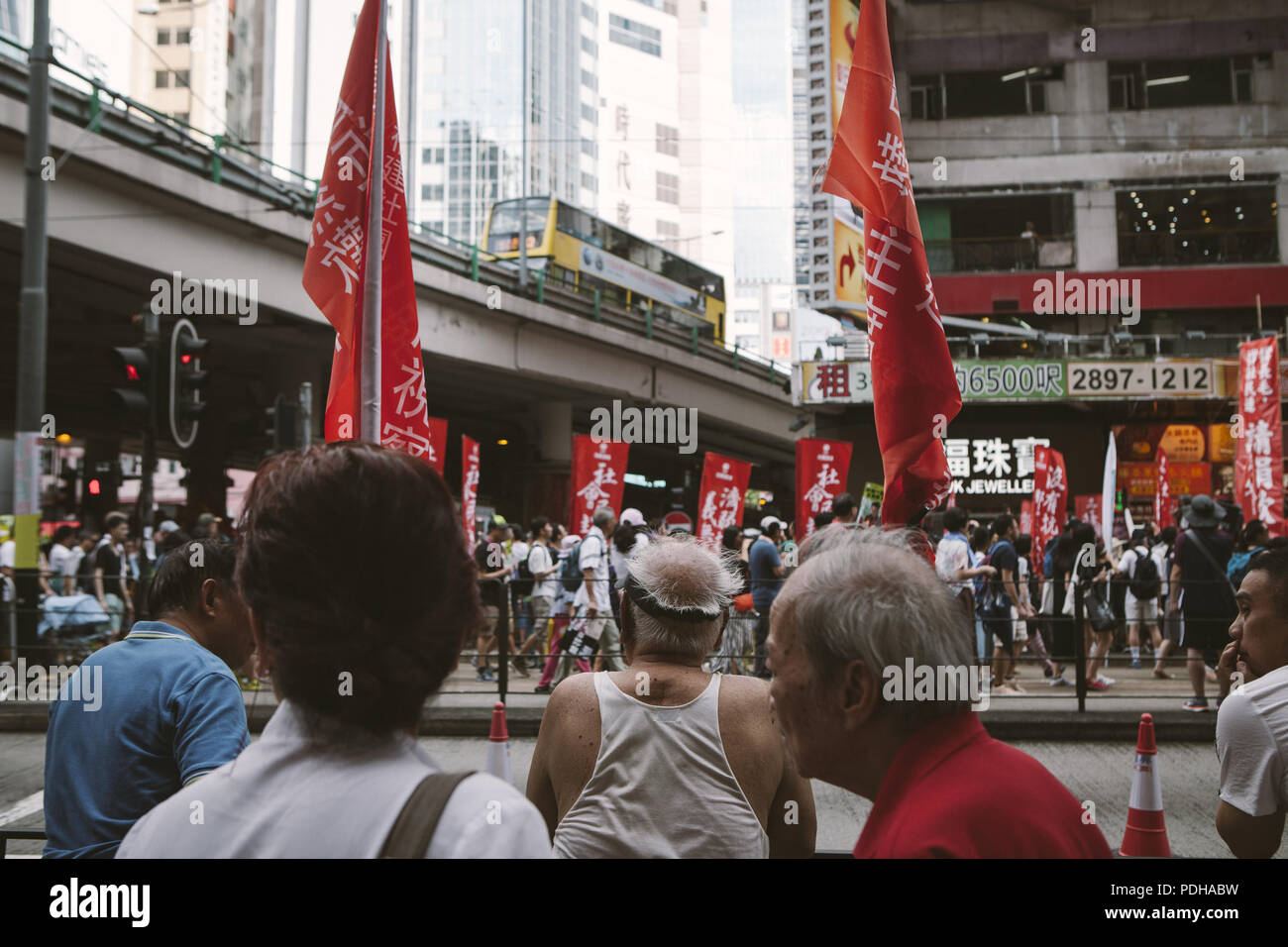 Hong Kong, Hong Kong. 1st July, 2017. People seen amazed by a stretch of both pro-China and pro-Hong Kong signs.Thousands came together and demonstrated to mark the 20th anniversary of the Handover from Britain to China, Hong Kong's return to China on July 1st 1997. The protestors marched through sun and rain from Victoria Park to Admiralty, taking a stand on a variety of human-rights-related causes. Credit: Viola Gaskell/SOPA Images/ZUMA Wire/Alamy Live News - Stock Image