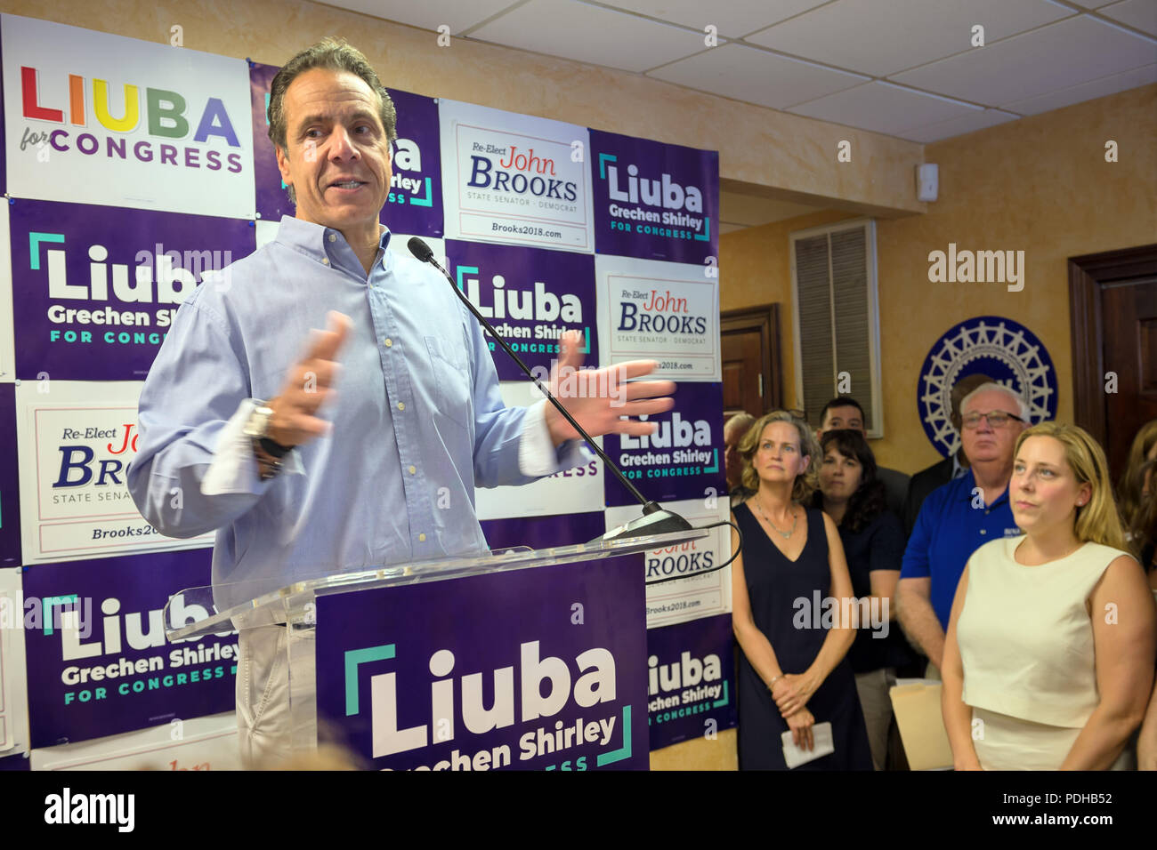 Massapequa, New York, USA. 5th Aug, 2018. L-R, Governor ANDREW CUOMO speaks at podium and endorses candidates, as LAURA CURRAN, Nassau County Executive; NY Senator JOHN BROOKS; and LIUBA GRECHEN SHIRLEY, Congressional candidate for NY 2nd District; and supporters listen at joint campaign office opening, aiming for a Democratic Blue Wave in November midterm elections. Credit: Ann Parry/ZUMA Wire/Alamy Live News - Stock Image