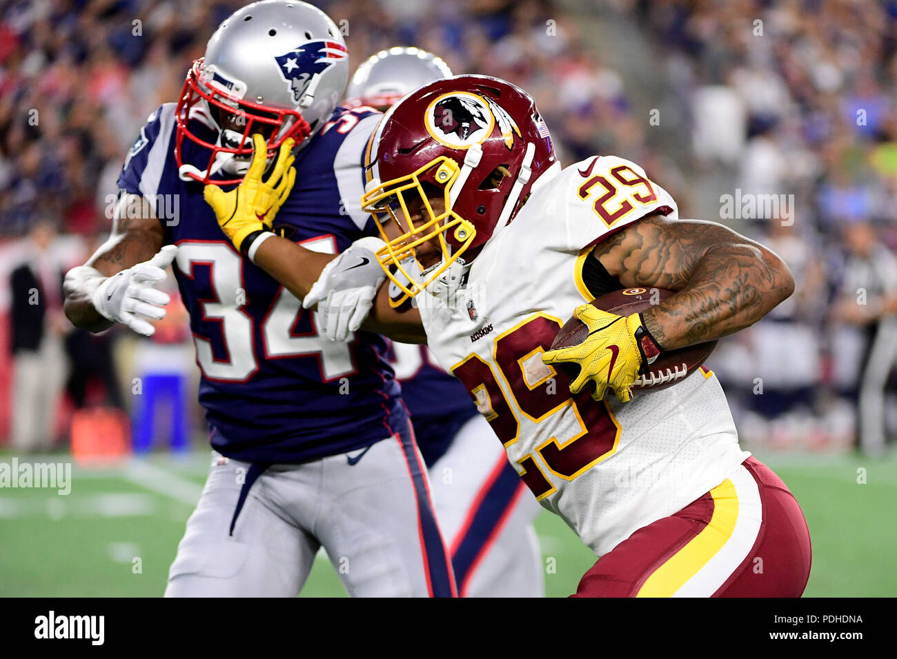 August 9, 2018: Washington Redskins running back Derrius Guice (29) stiff arms New England Patriots ...