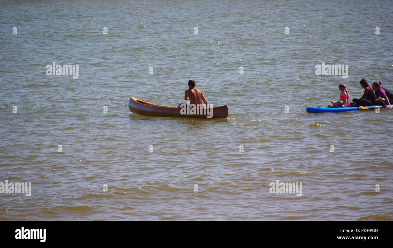 Man Rowing A Wooden Canoe In The Sea At Sidmouth On A Summers Day