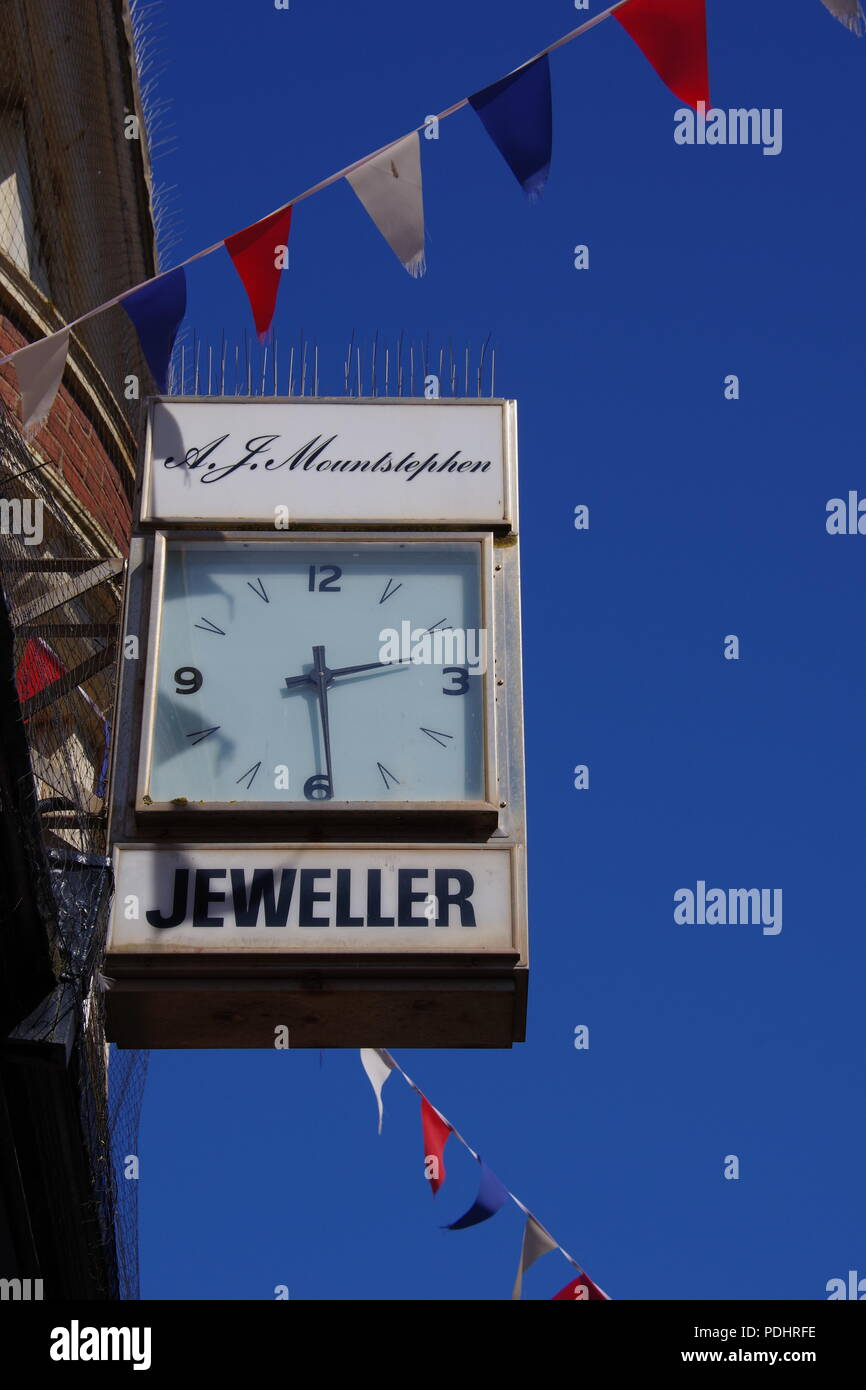 Jeweller Shop Clock on a Sunny Day with Red, White and Blue Bunting. Sidmouth, East Devon, UK. - Stock Image