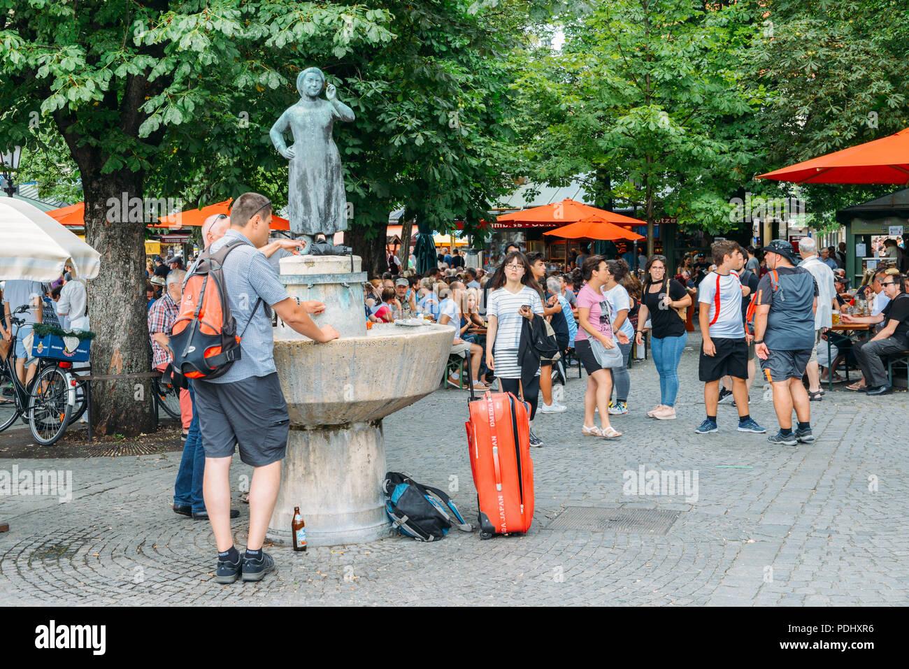Munich, Germany - July 29, 2018: Tourists next to statue of actress Liesl Karl Town at Munich's Viktualienmarkt - Stock Image