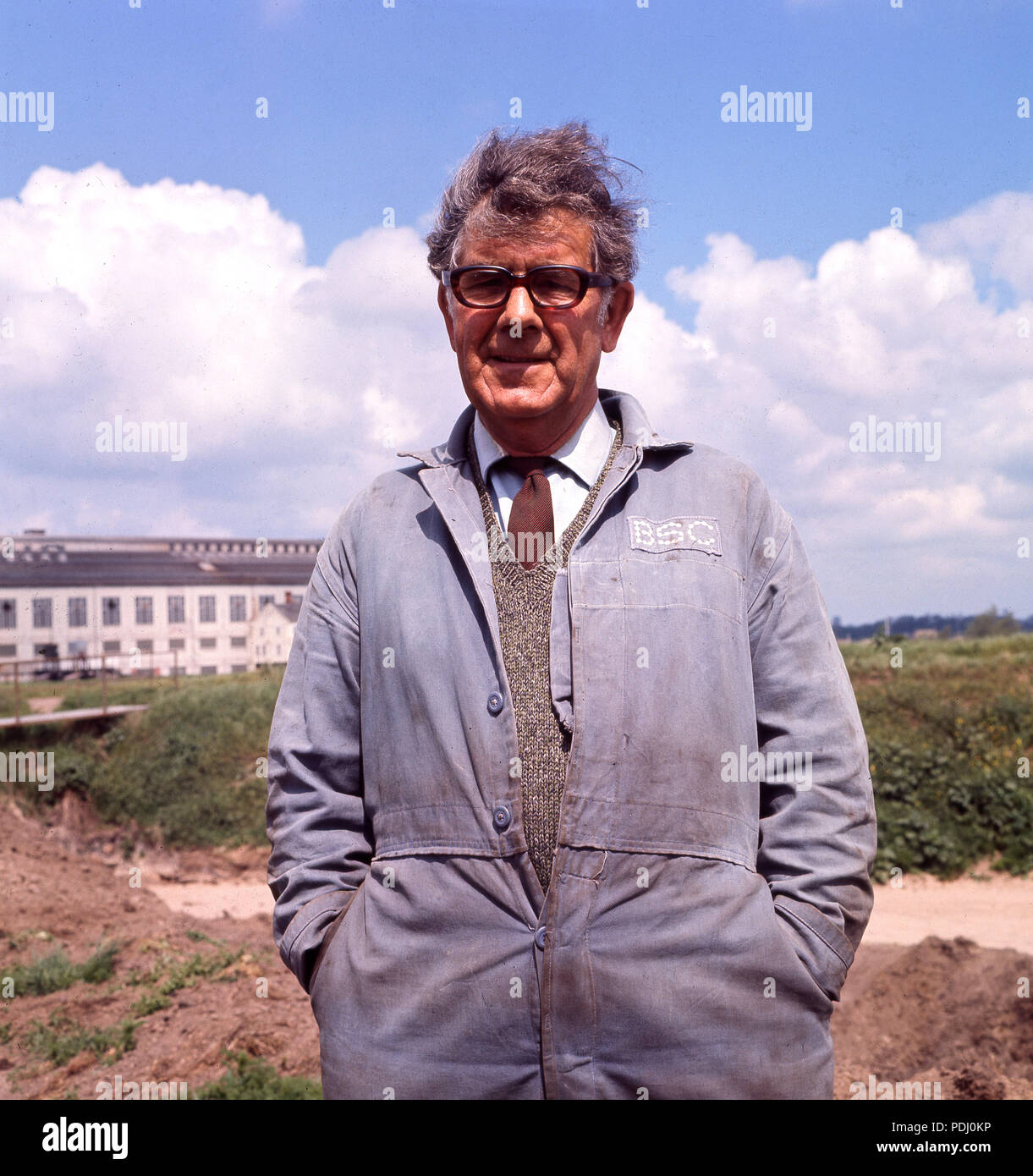 1960s, man standing outdoors in a shirt and tie and work clothes, the blue/grey overalls of the nationalised British Steel Corporation (BSC), England, UK. - Stock Image