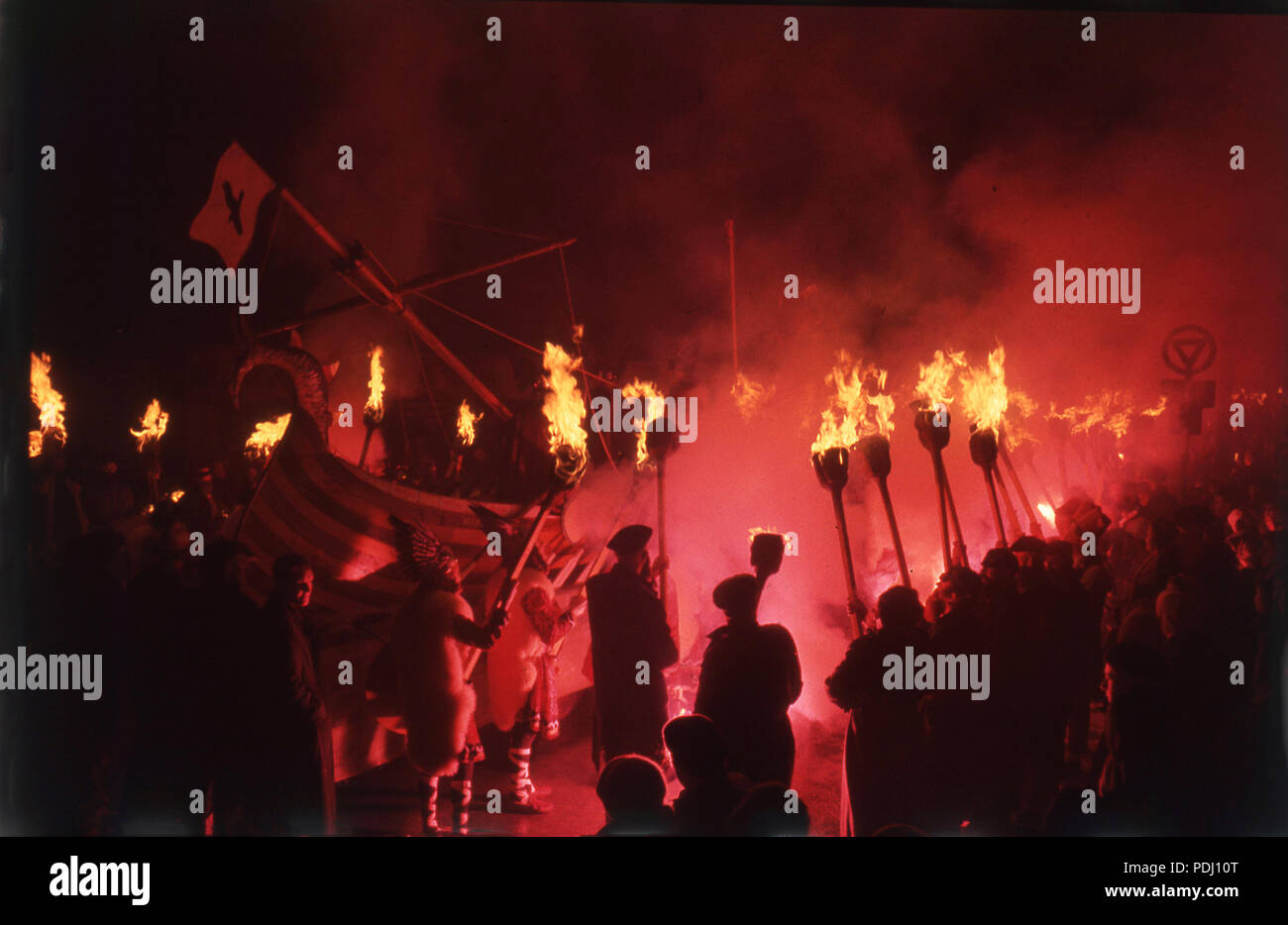 1960s, night-time and a crowd watch a re-enactment of a viking raid from a longship, with burning torches and fire, Scotland. The vikings were Norse seafarers, a fierce tribe of peoples who raided the UK from their Northern homelands and are an important part of British history. - Stock Image