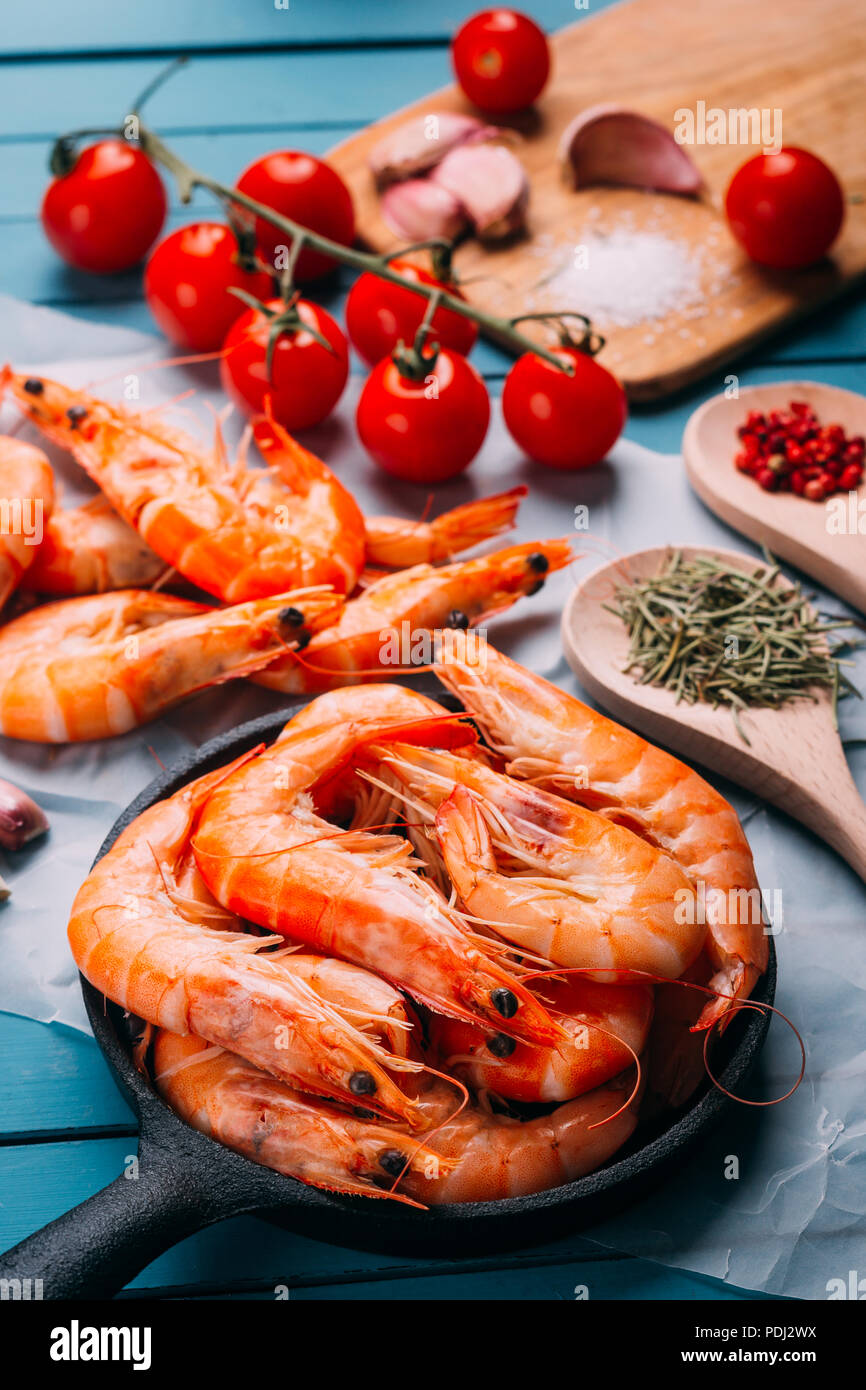 High angle view of blue wooden table full of prawns and some ingredients for seasoning and vegetables to mix them, concept of recipes and restaurants - Stock Image