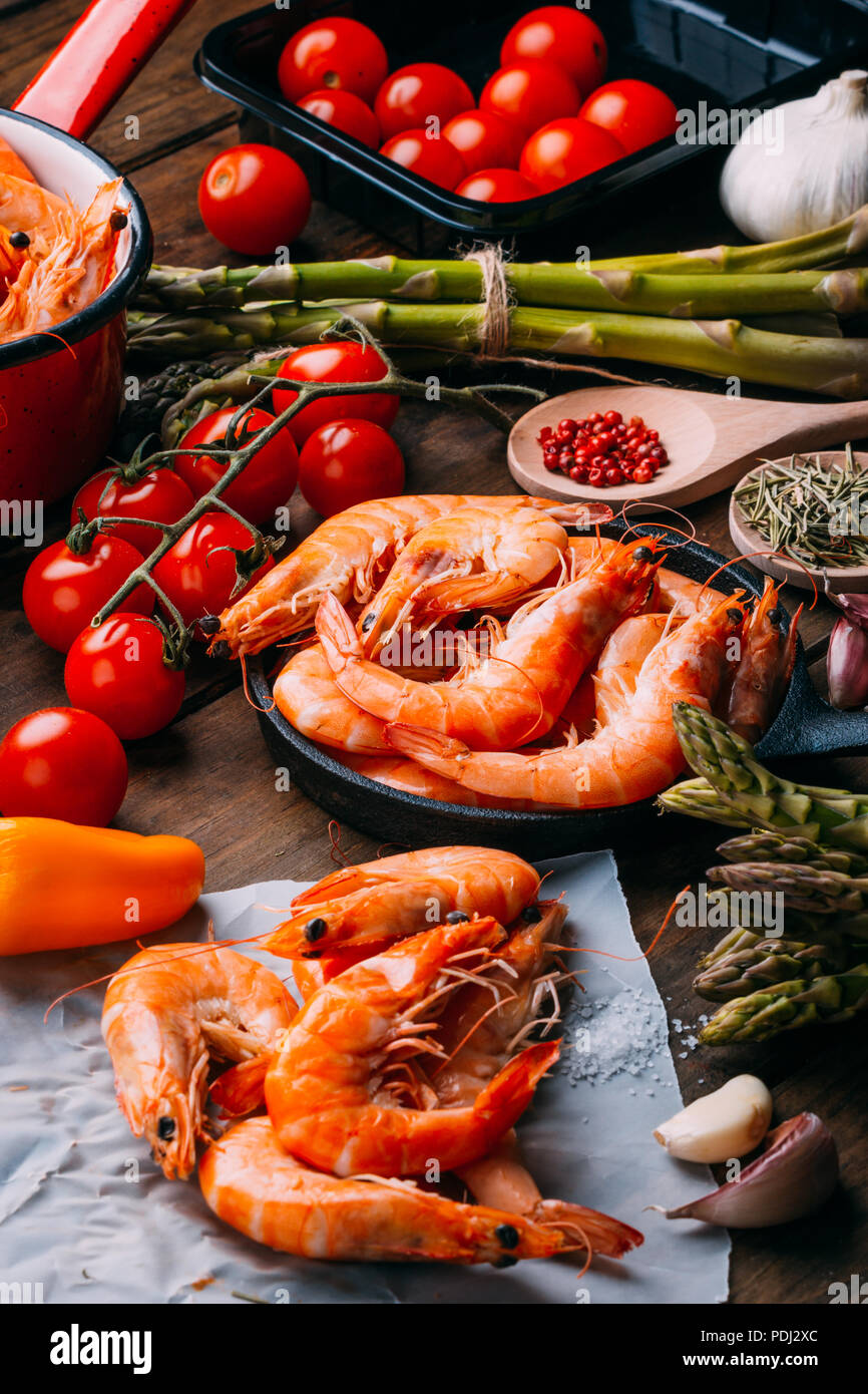 Top view of rustic wooden table full of prawns and some ingredients for seasoning and vegetables to mix them - Stock Image