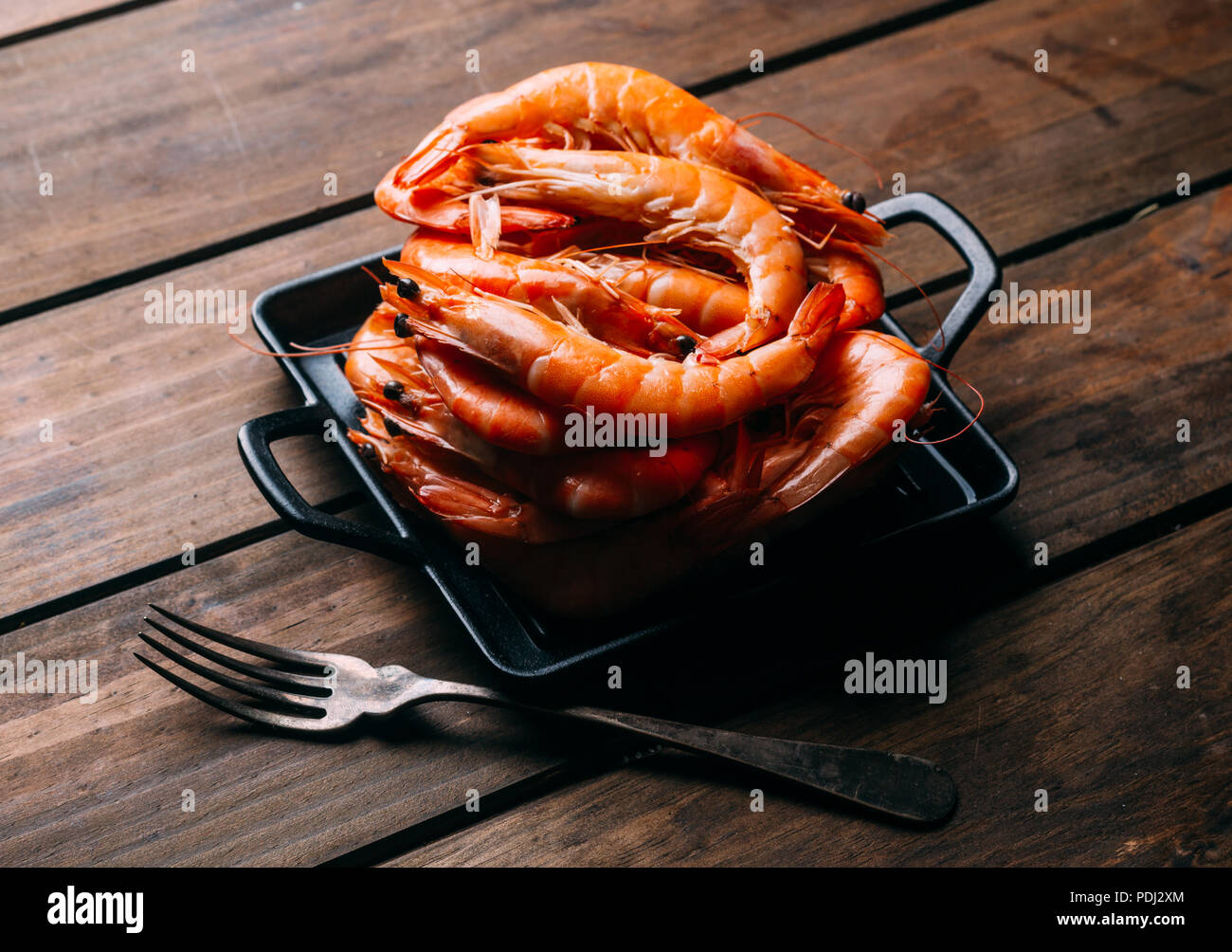 Delicious prawns in a pan on a wooden table - Stock Image