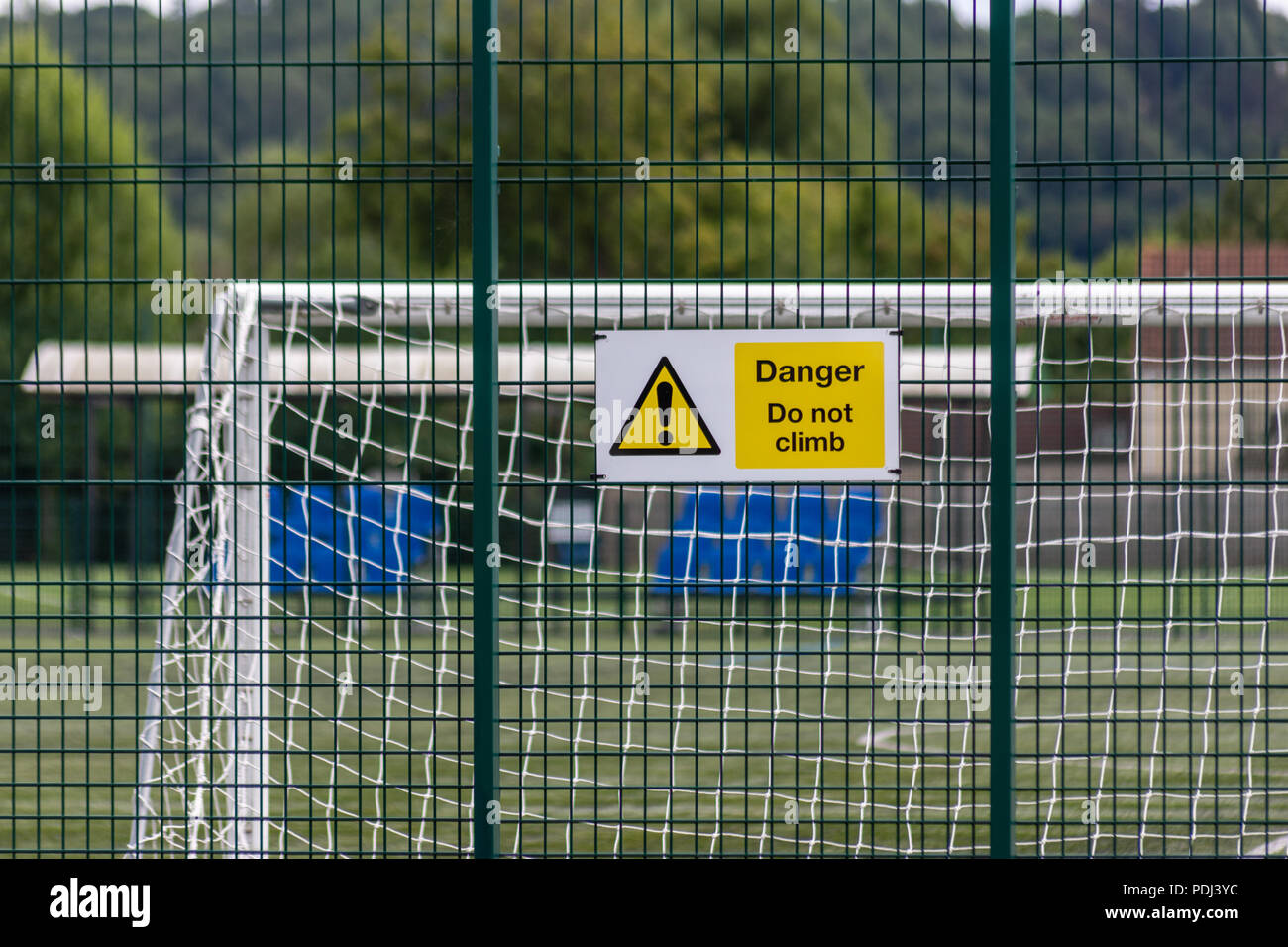 Sign warning of danger on a rigid metal grid fence with football goal posts visible behind the wire fence - Stock Image