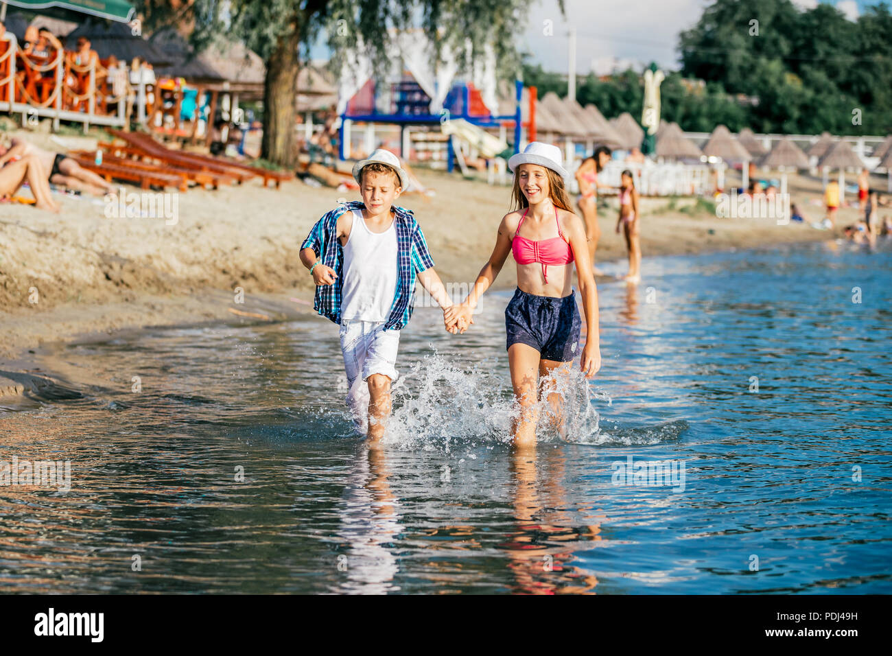 Happy children playing in the sea. Kids having fun outdoors. Summer vacation and healthy lifestyle concept - Stock Image