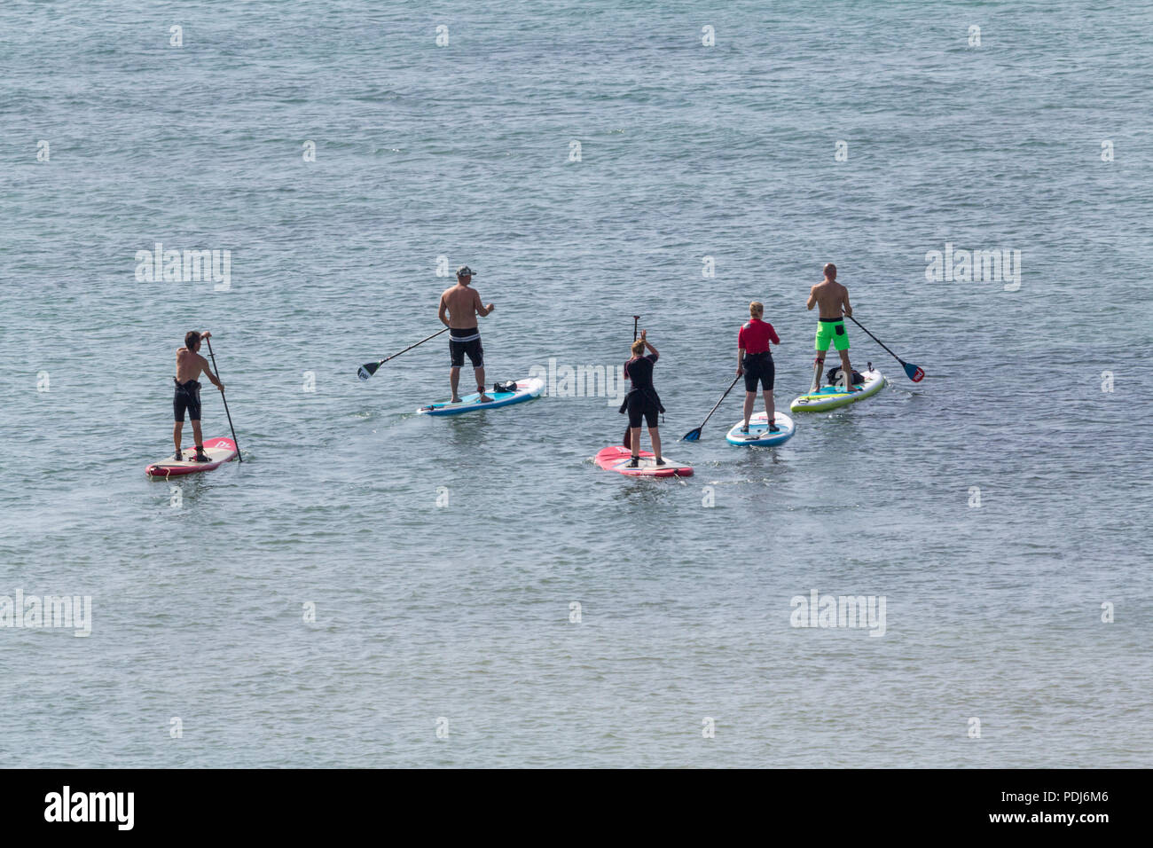 Paddle boarders near seven sisters cliffs UK on a hot Saturday morning 2018 summertime heatwave calm sea hot sun gentle water sport activity. - Stock Image