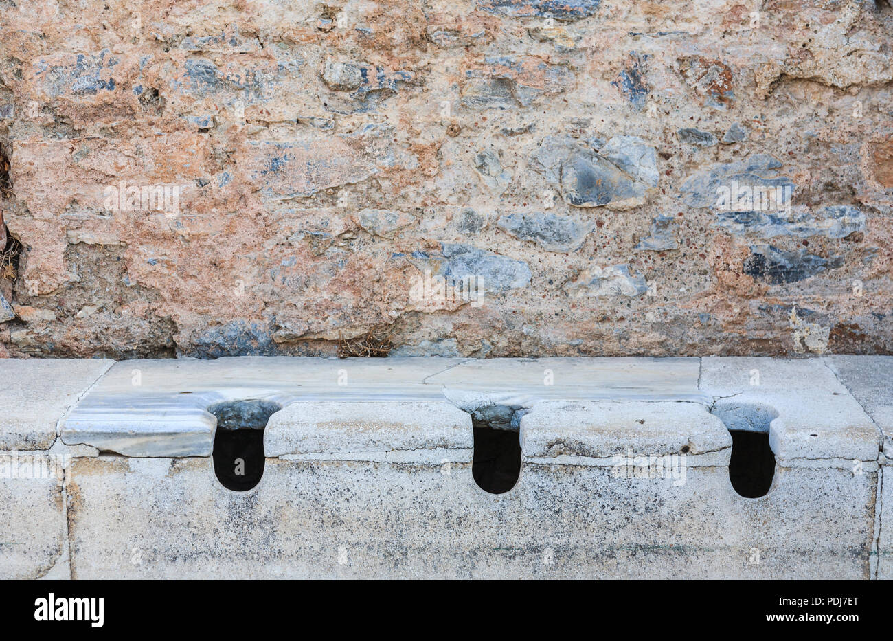 Stone communal toilets at Ephesus, an ancient Greek city settlement archaeological site on the Ionian coast near Selçuk, Izmir Province, Turkey Stock Photo
