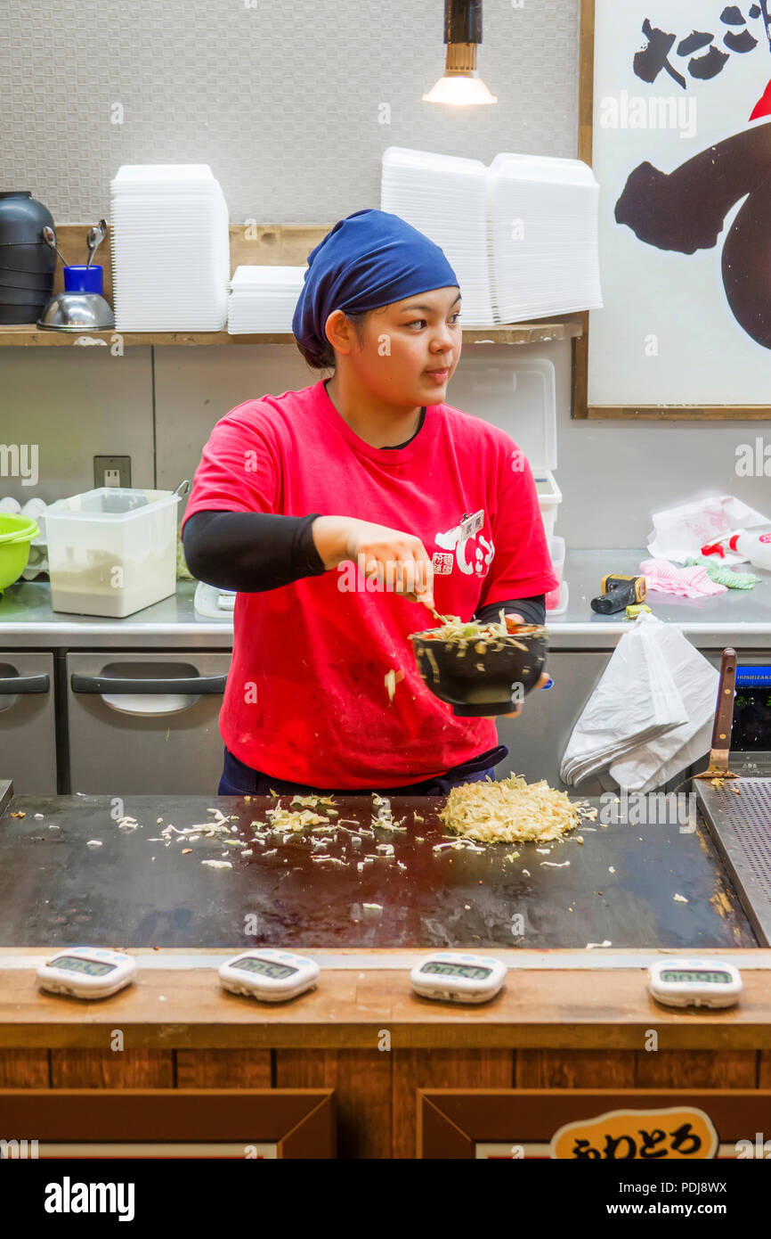 Fast food worker prepares dish for sale as customers watch Osaka Japan Asia - Stock Image
