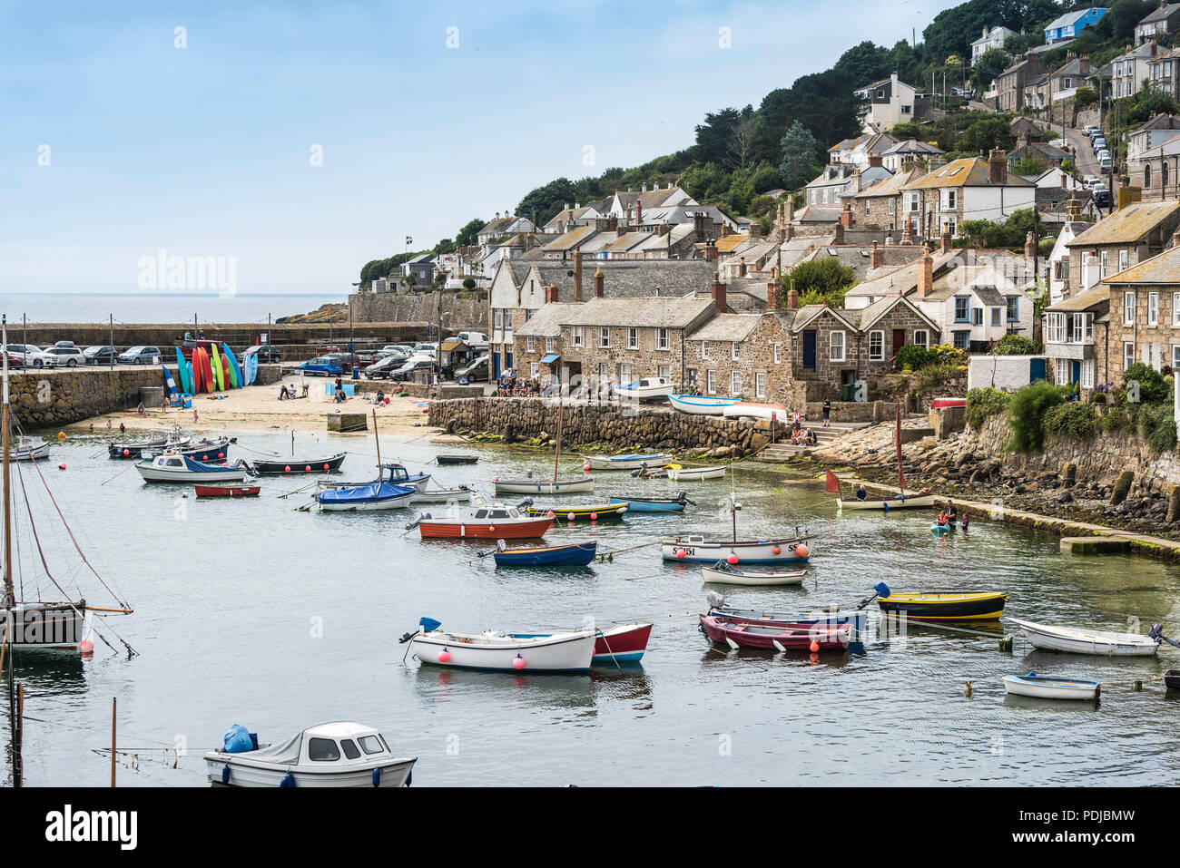 Small boats moored in the quaint harbour in Mousehole in Cornwall. - Stock Image