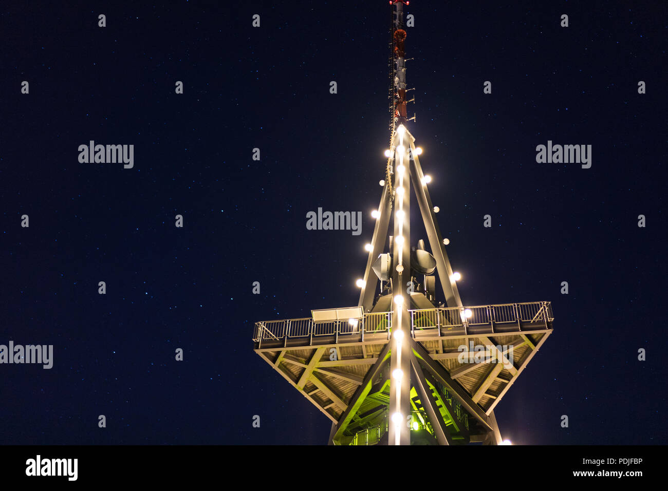 tv tower at night with lights and stars iconic low angle view - Stock Image
