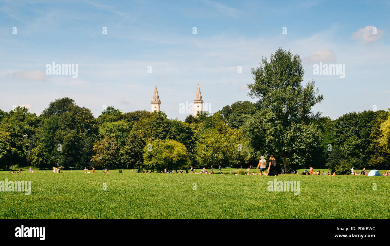 Munich, Germany - July 29, 2018: Munich skyline from Englischer Garten, German. Locals and tourists enjoy a warm summer day in the park - Stock Image