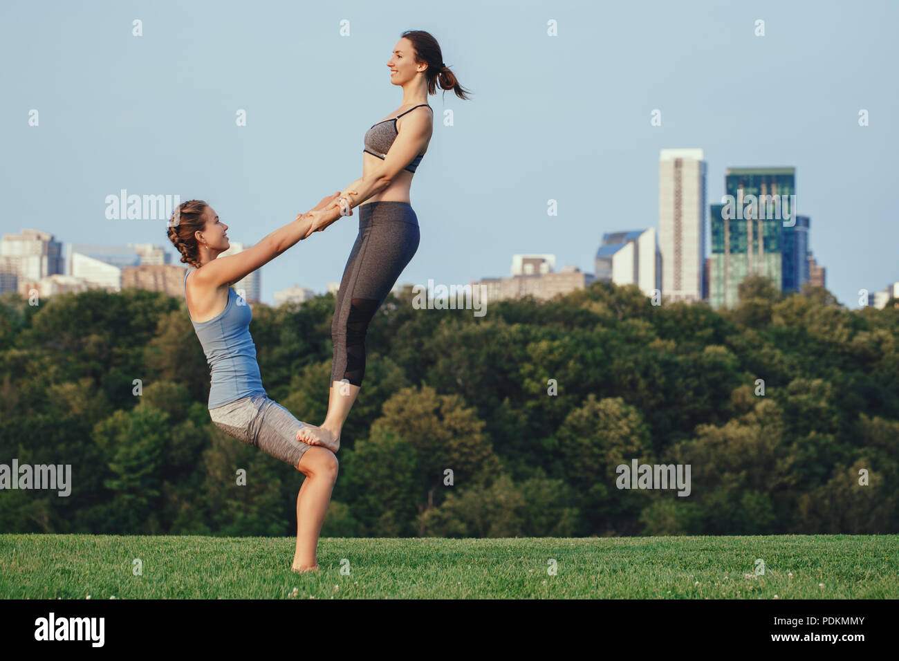 Two young beautiful Caucasian women yogi doing thigh stand acro yoga pose. Women doing stretching workout in park outdoors at sunset. Healthy lifestyl - Stock Image