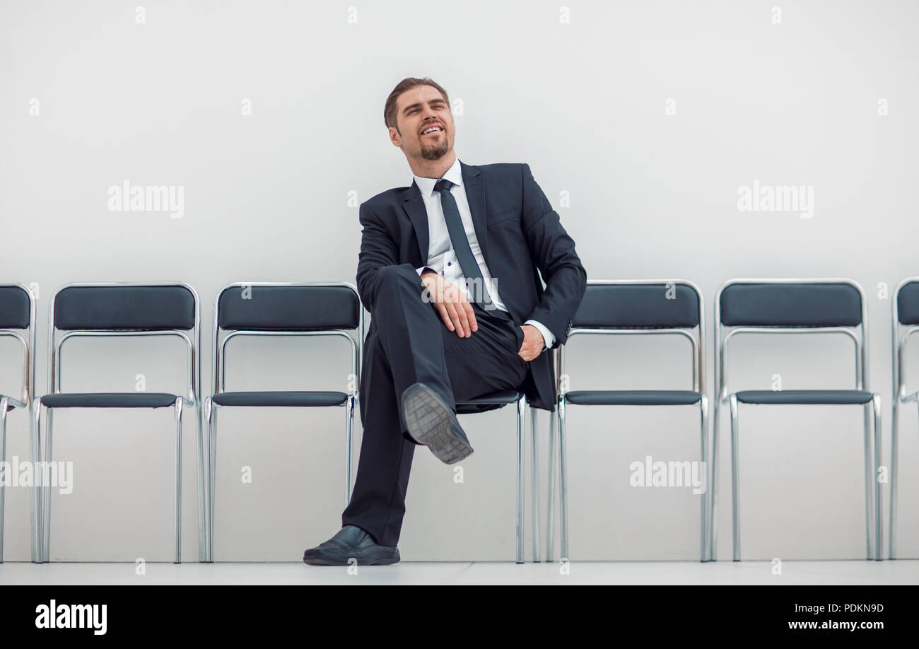 thoughtful businessman sitting in the office hallway - Stock Image