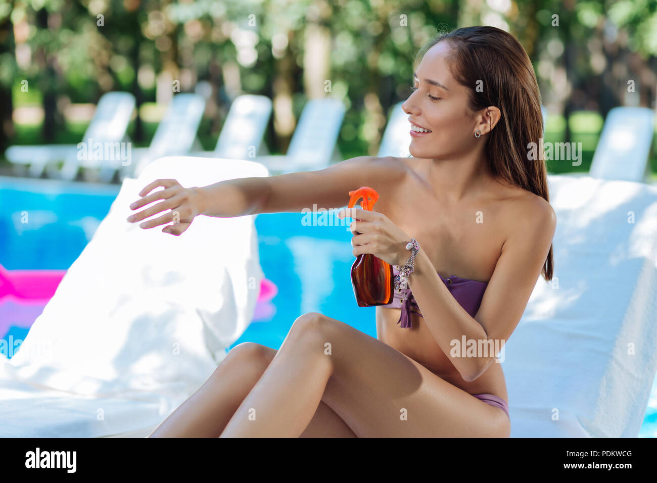 Appealing woman thinking abut healthcare while using sun protection - Stock Image