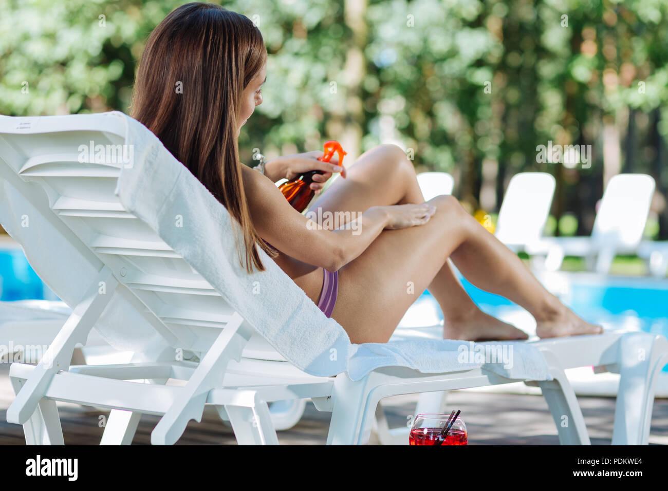 Slim successful model using sun protection cream - Stock Image