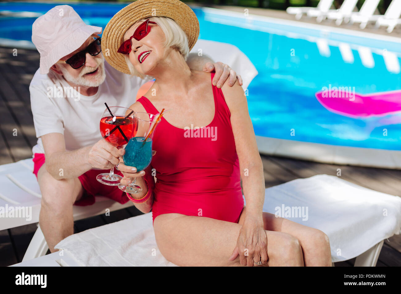Mature woman wearing red swimming suit looking at her husband - Stock Image