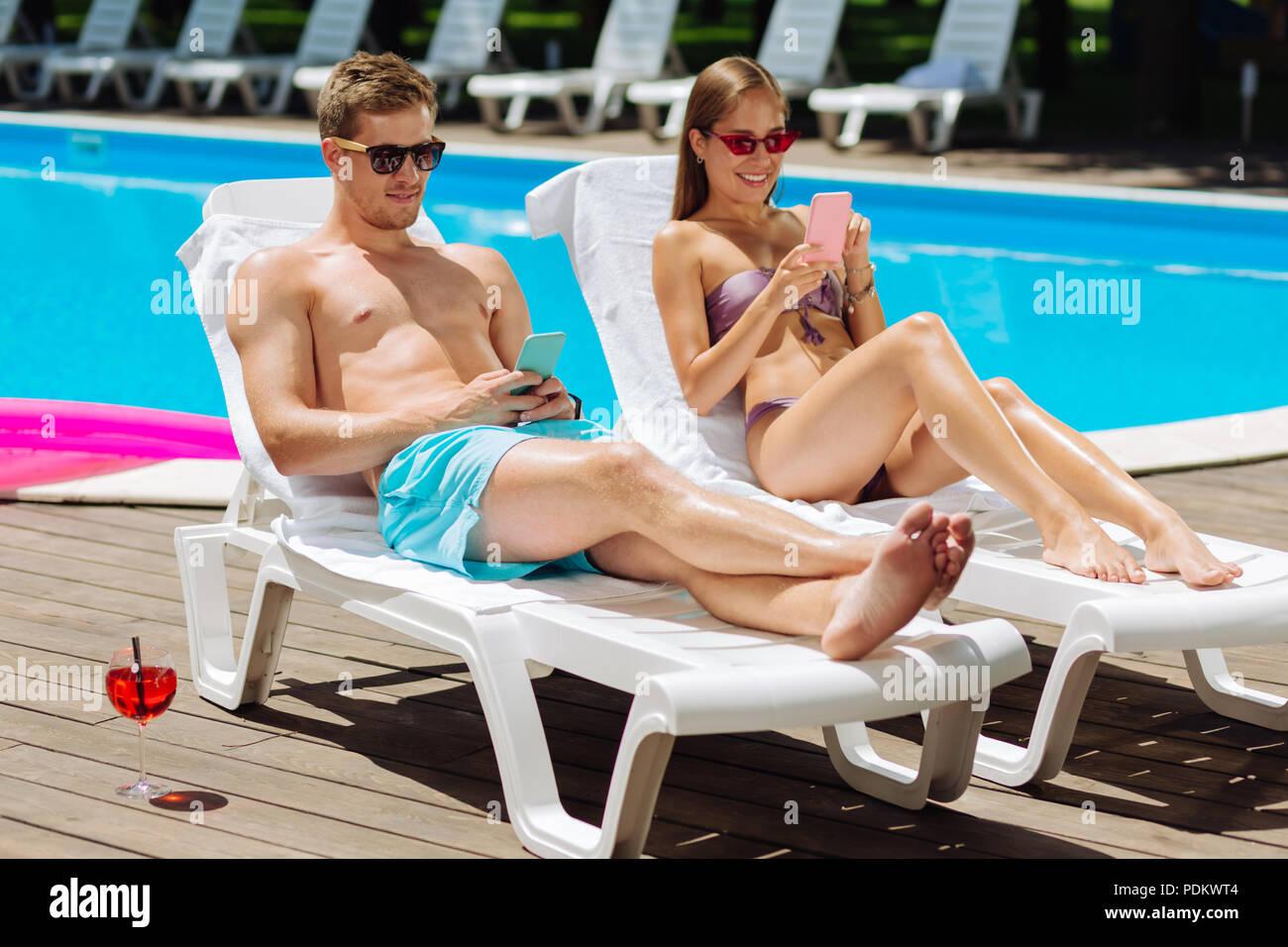 Modern boyfriend and girlfriend using their phones sunbathing - Stock Image