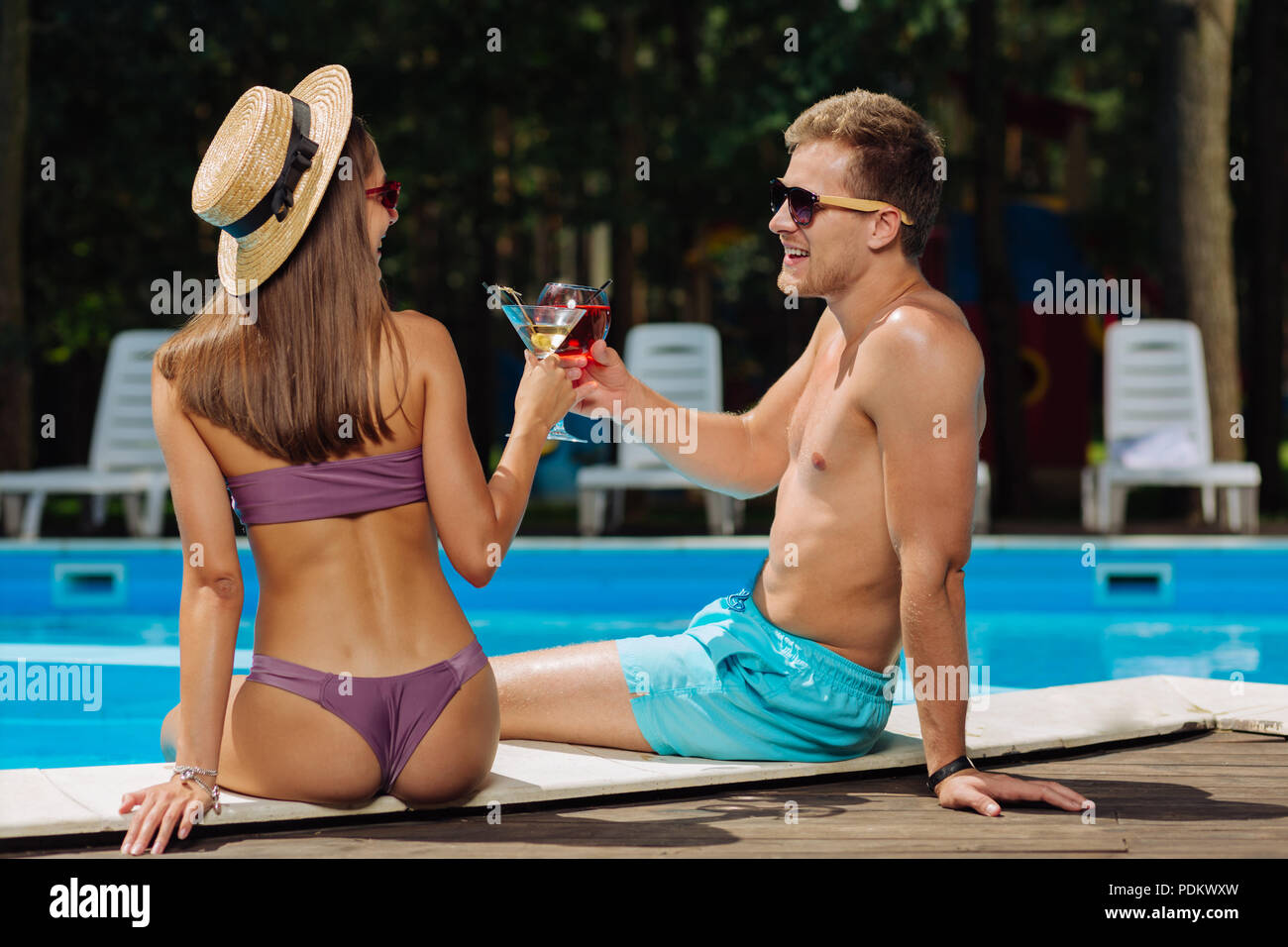 Slim woman wearing purple swimming suit sitting near boyfriend - Stock Image