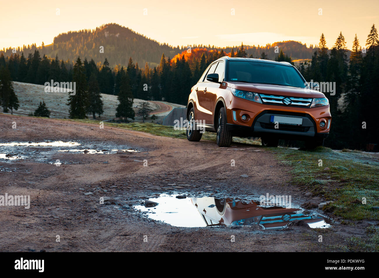Apuseni, Romania - OCT 15, 2017: orange Suzuki Vitara SUV on a country road in mountains at sunrise. beautiful autumn landscape with spruce forest.tra - Stock Image