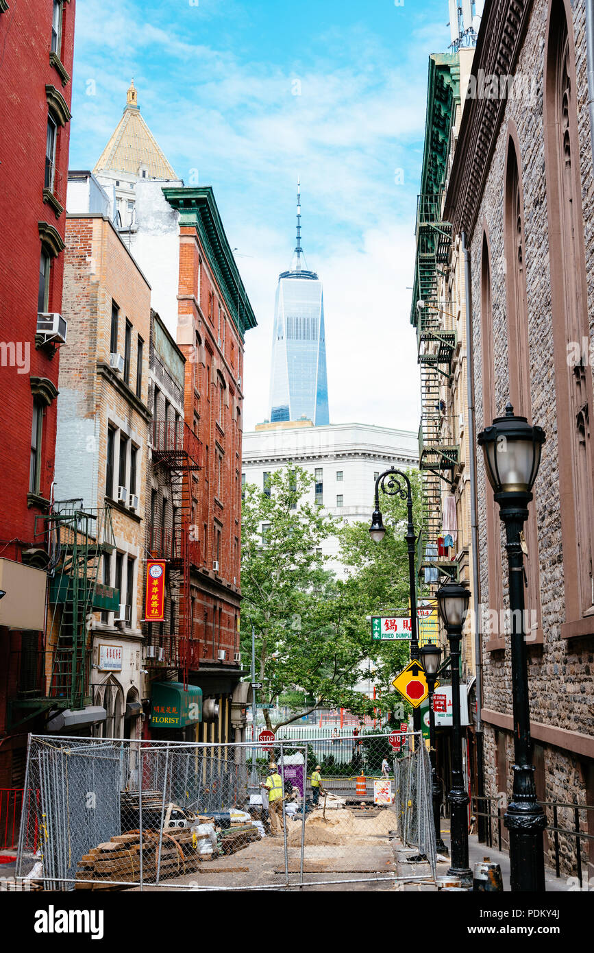 New York City, USA - June 20, 2018: Roadworks in Chinatown street in downtown of New York against One World Trade Center building - Stock Image