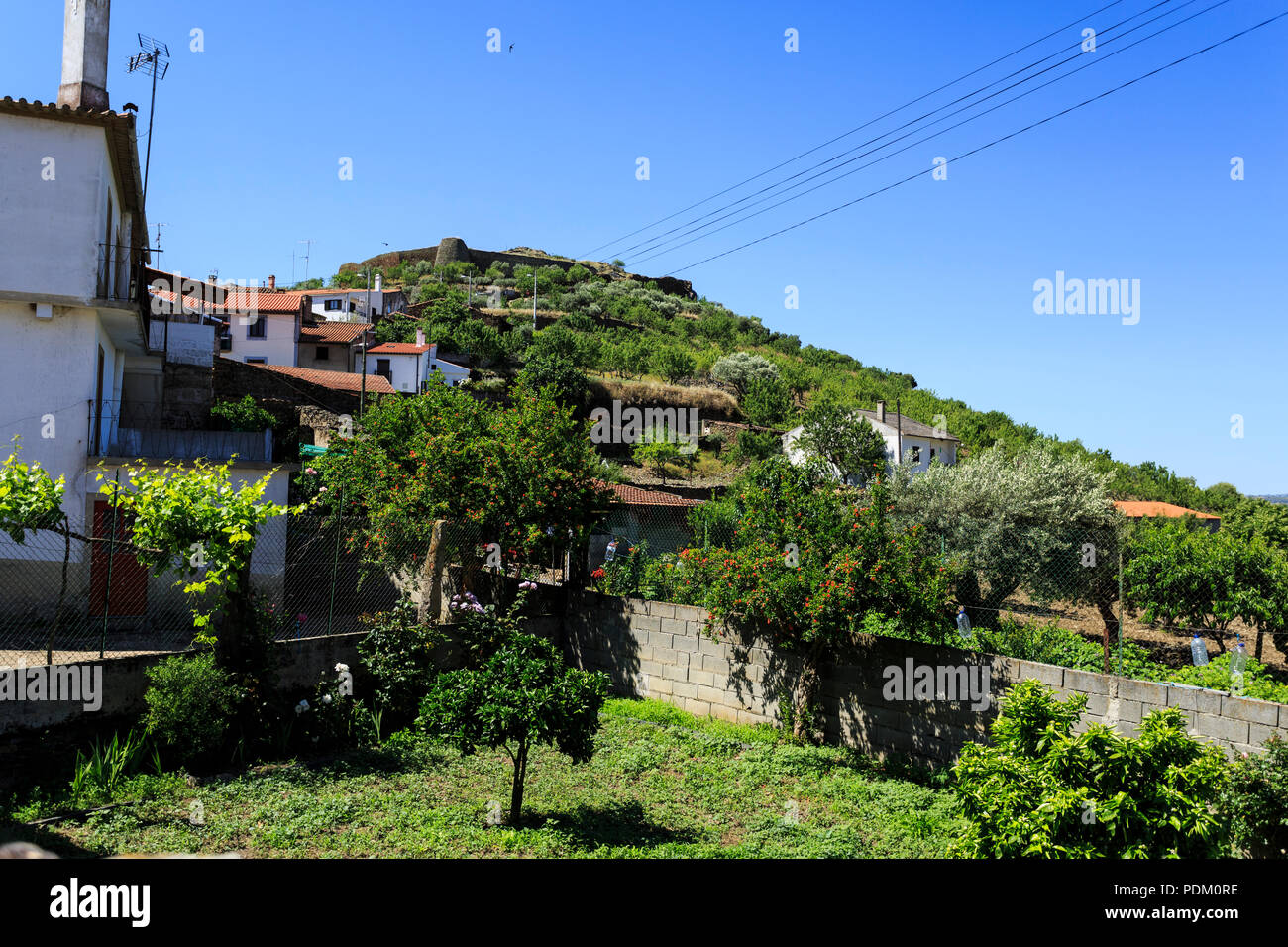 View of the medieval fortress walls of irregular polygonal form circling the hilltop and overlooking the settlement of Castelo Melhor, Portugal Stock Photo