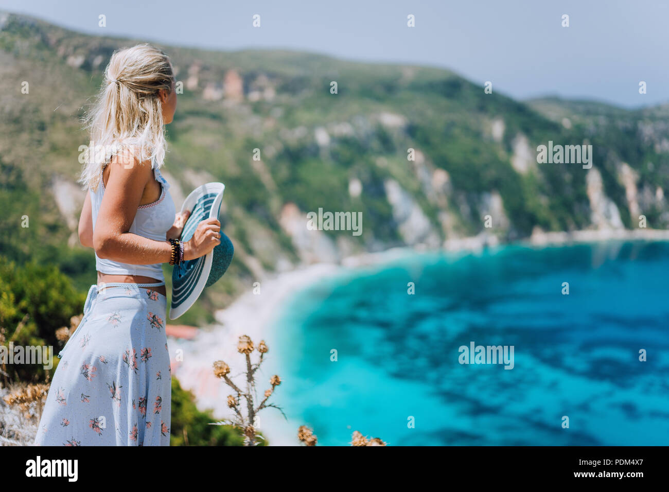 Young woman in front of Petani beach Kefalonia admiring highly excited picturesque panorama of emerald bay of Mediterranean sea and steep coastline island Greece - Stock Image