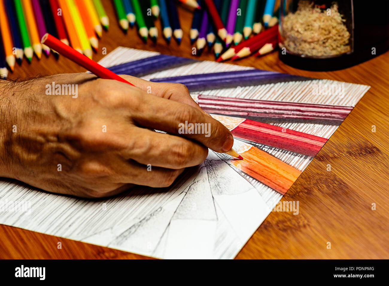 An Artists hand at work using colored pencils to draw colored pencils on white paper.  there is negative space for Copy. - Stock Image