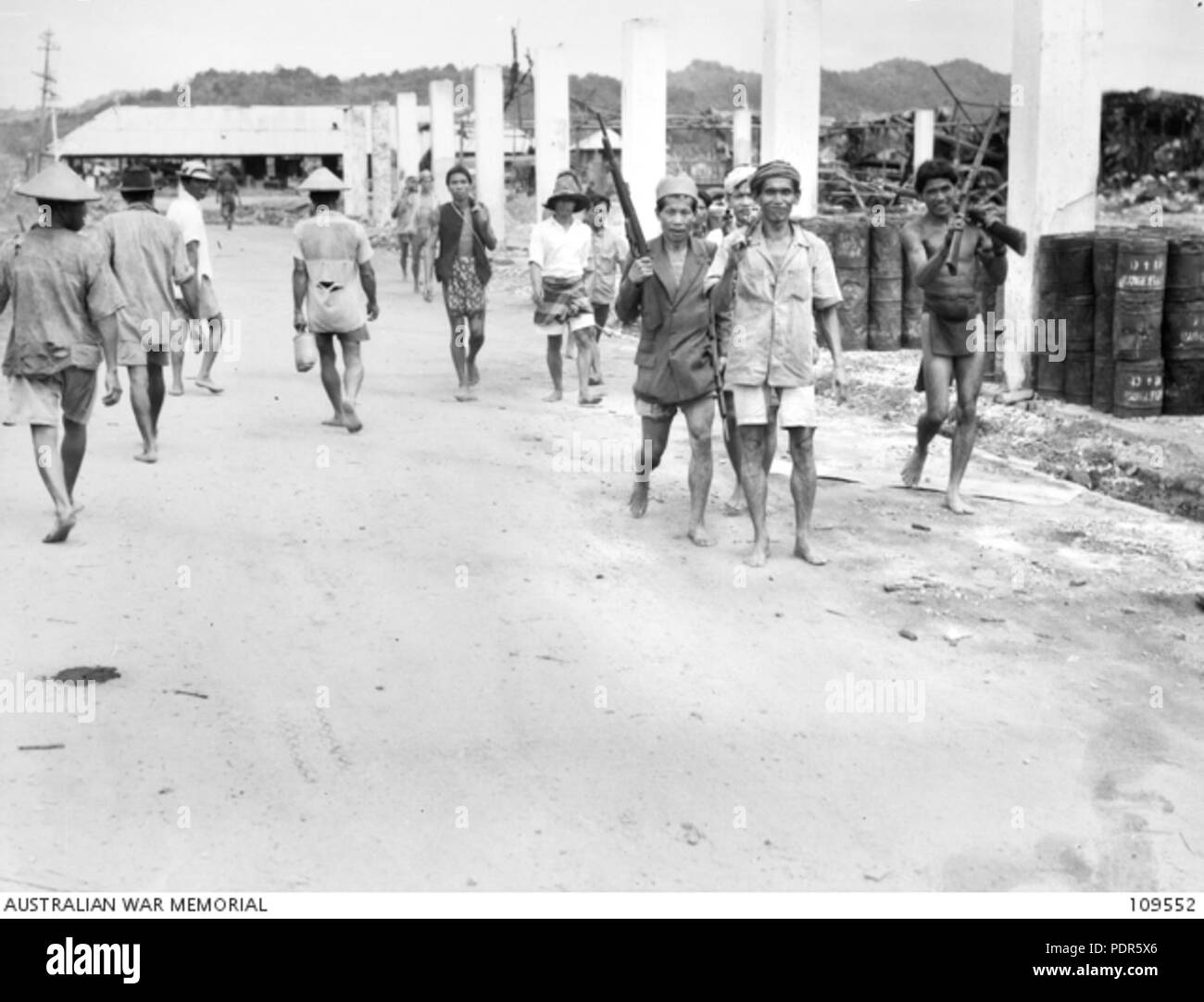 67 Indigenous peoples armed with Japanese rifles walking along a Brunei street - Stock Image