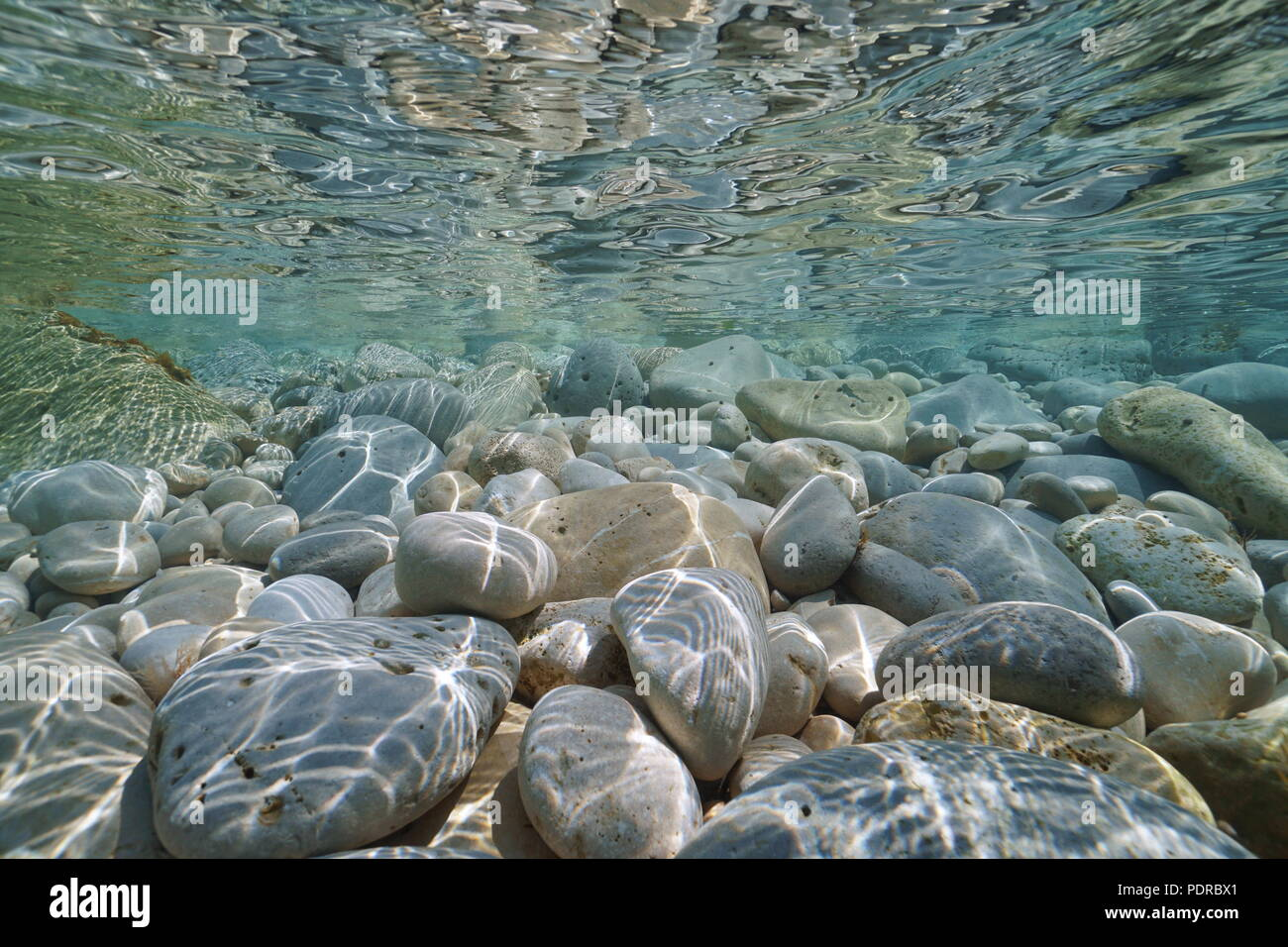 Pebbles and rocks below water surface in shallow water in the Mediterranean sea, underwater scene, Javea , Alicante, Valencia, Spain - Stock Image
