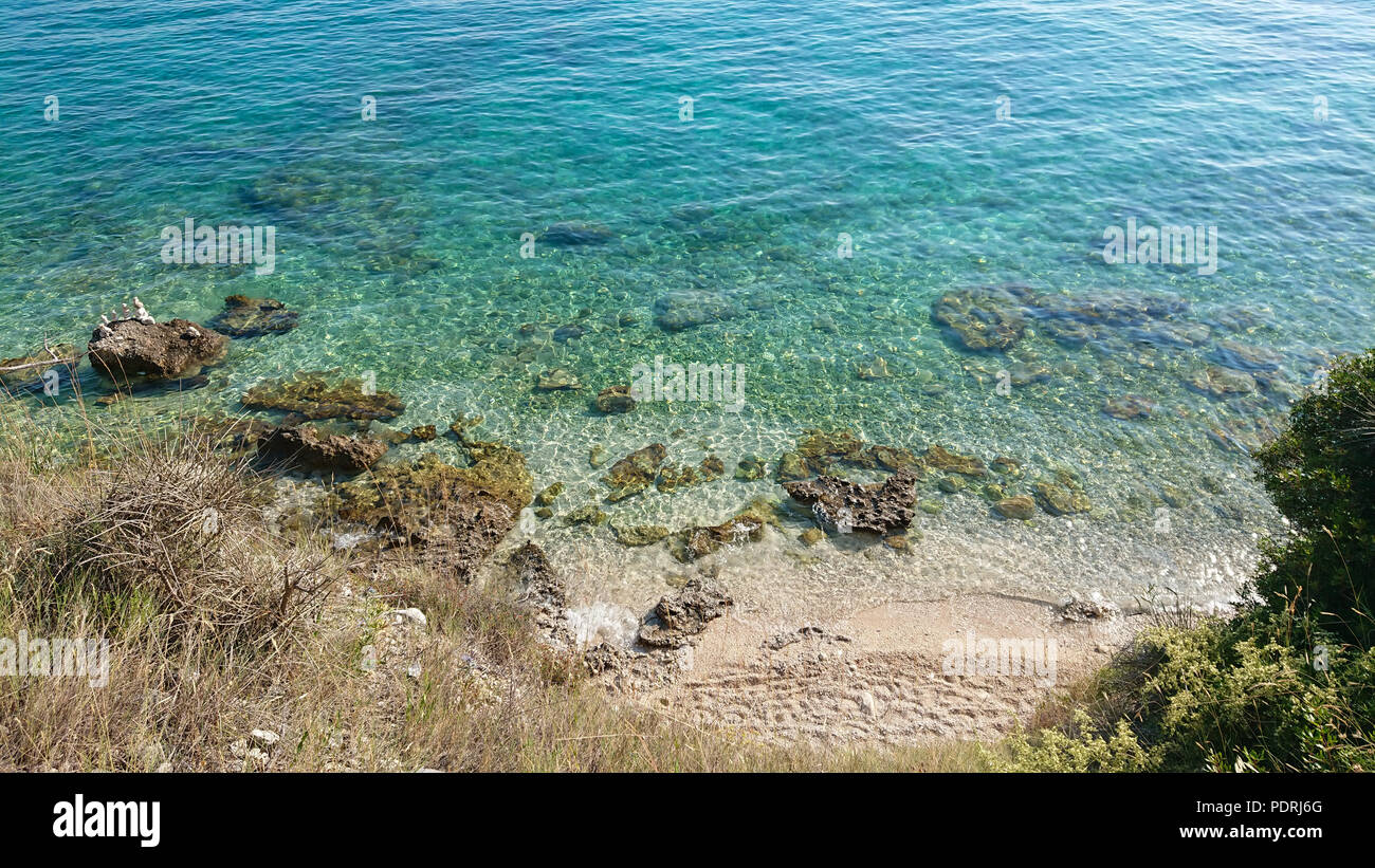 Rocky beach, blue transparent sea - Stock Image