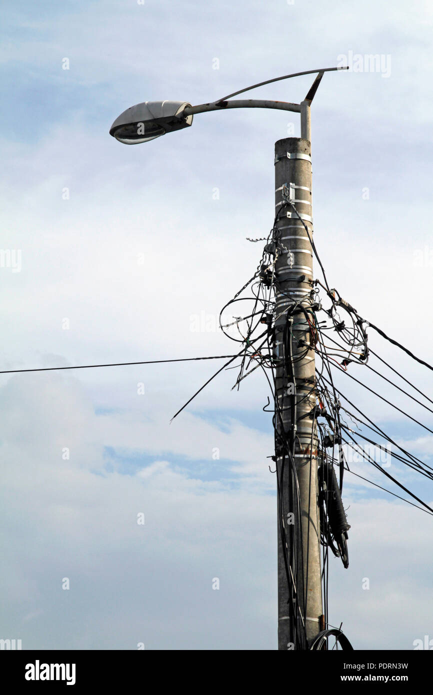 Entangled power lines attached to a street light in Romania - Stock Image