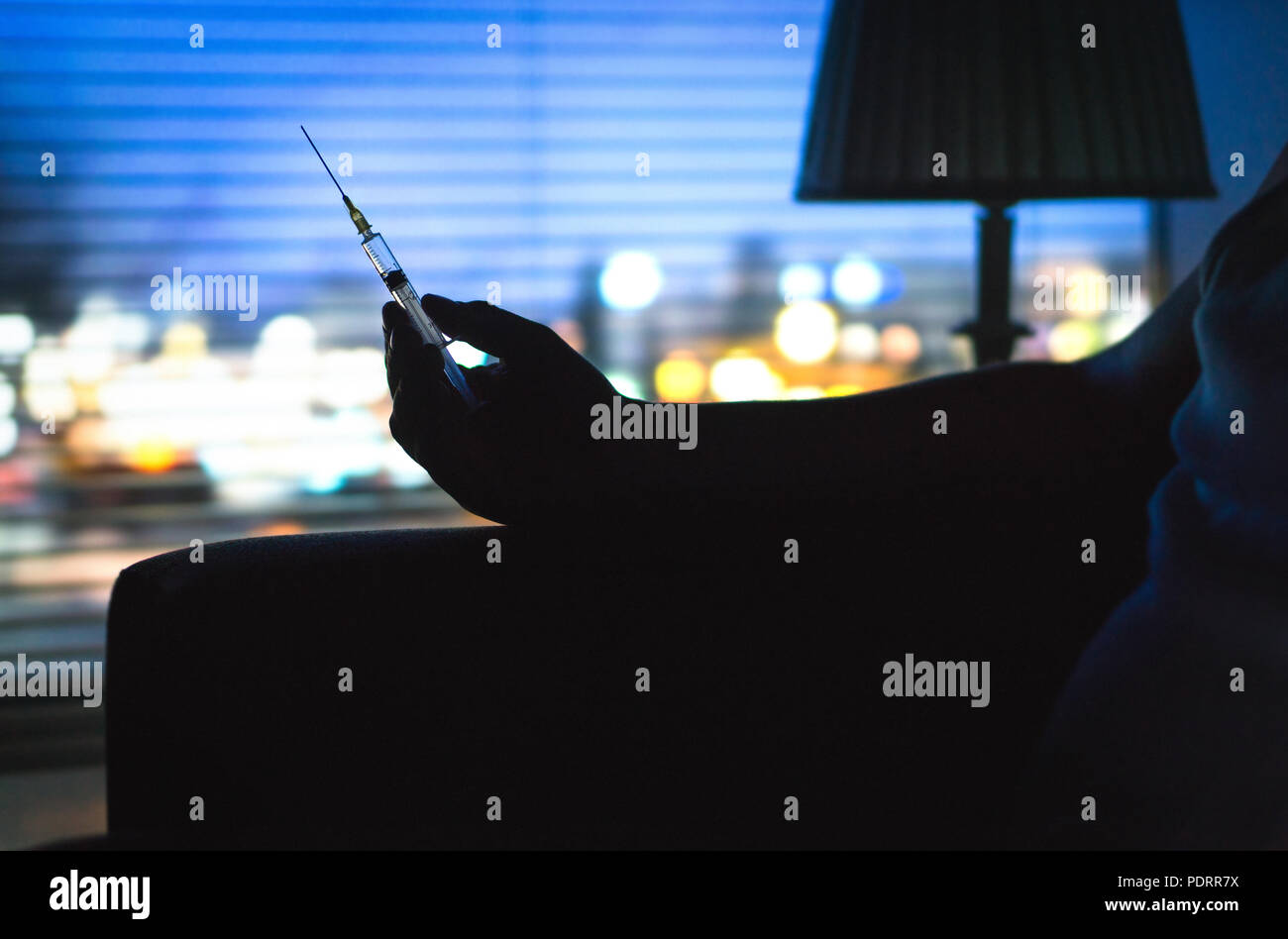 Drug addict with heroin syringe silhouette in dark. Hand holding needle late at night. City lights background from home apartment window. - Stock Image