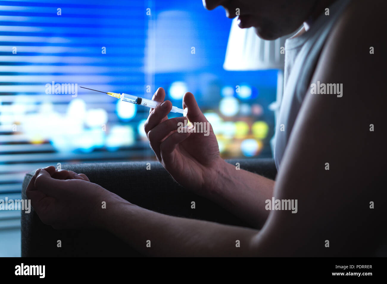 Heroin addict in dark late at night using drugs. Young man with bad drug problem using dirty needle. Dramatic addiction, overdose and substance abuse. - Stock Image