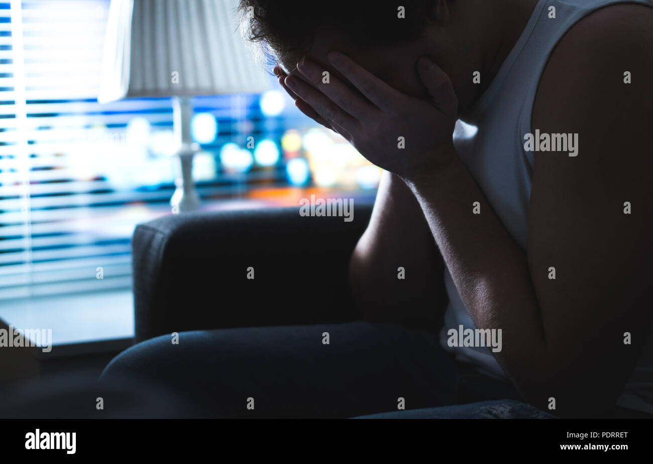 Sad and unhappy man covering face with hands in dark by window. Burnout, overwork or bankruptcy. Heartbroken person missing at night. - Stock Image